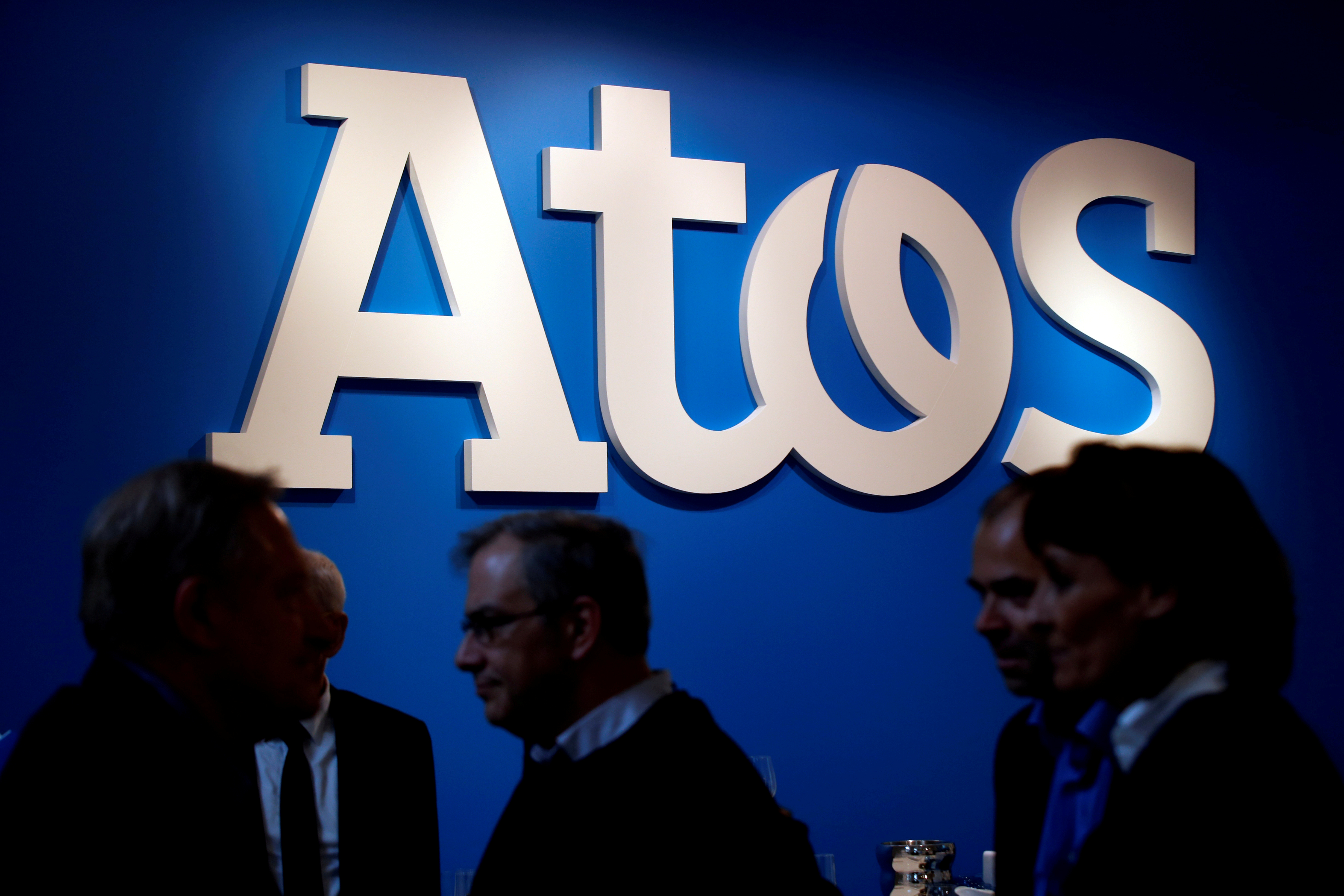 People walk in front of Atos company's logo during a presentation of the new Bull sequana supercomputer in Paris, France, April 12, 2016. REUTERS/Philippe Wojazer