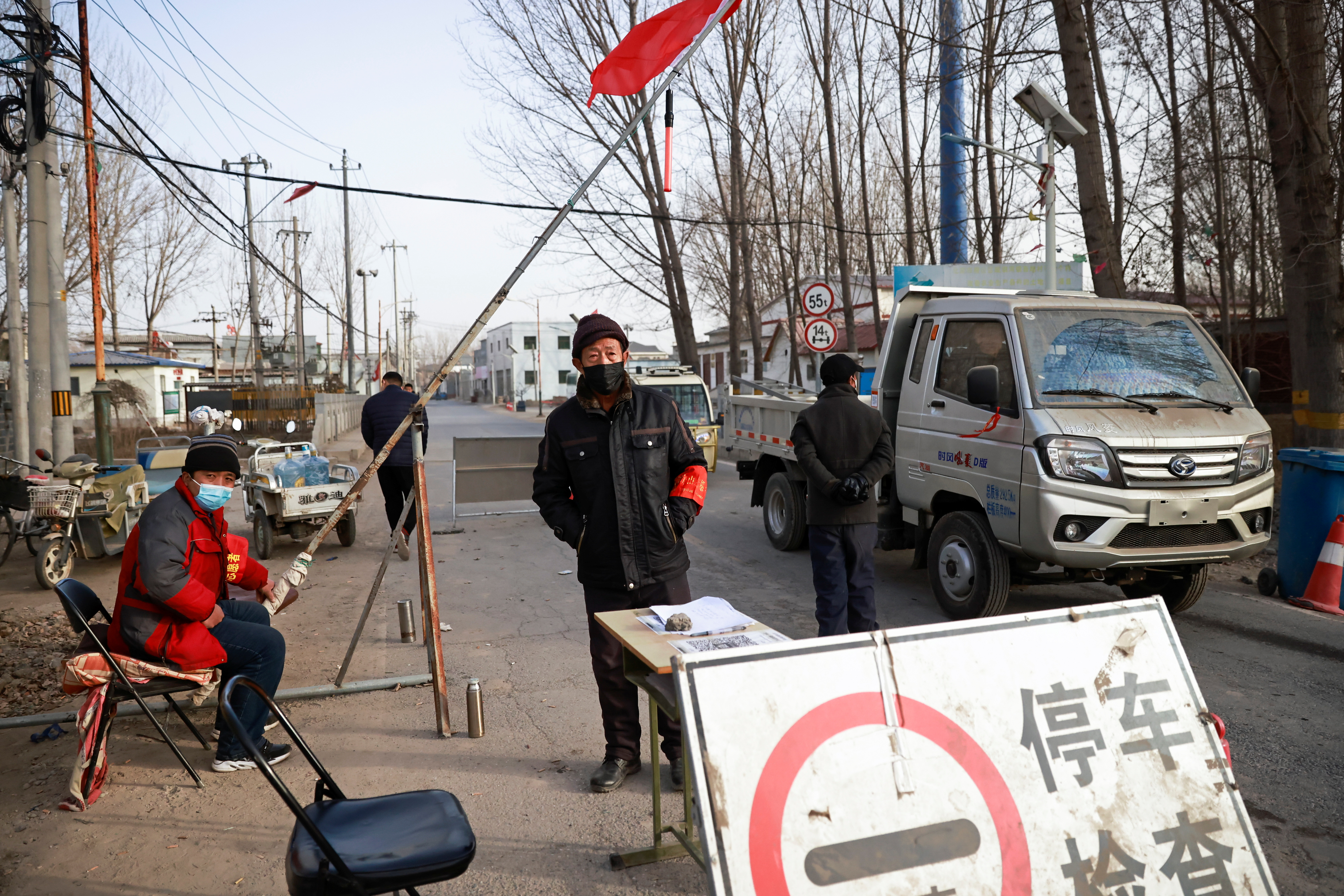 Volunteers stand at a checkpoint on a road leading into their village, following the coronavirus disease (COVID-19) outbreak, on the outskirts of Beijing near the provincial border with Hebei province, China January 12, 2021. REUTERS/Thomas Peter