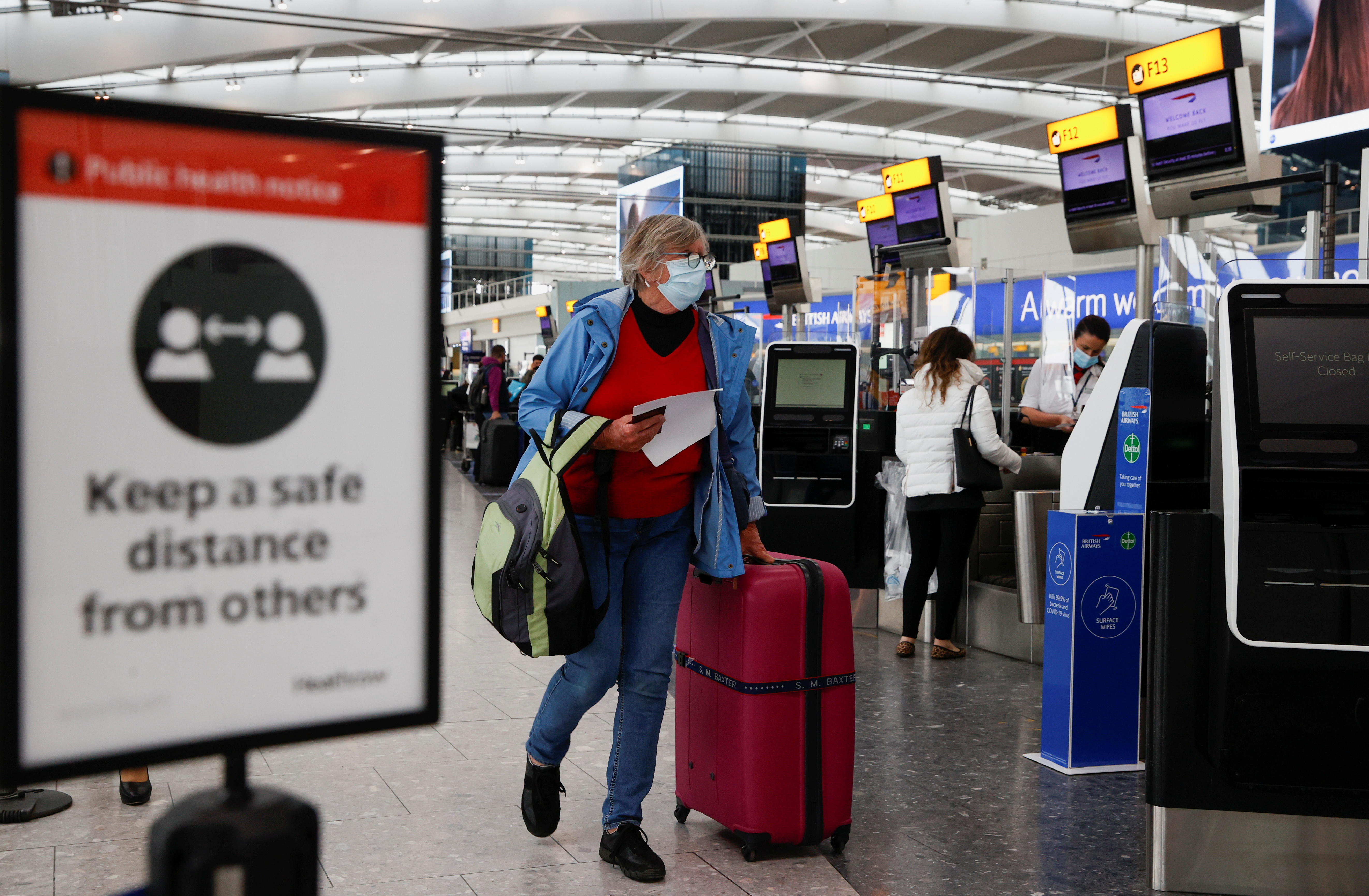 A passenger walks with her luggage at the Terminal 5 departures area at Heathrow Airport in London, Britain, May 17, 2021. REUTERS/John Sibley