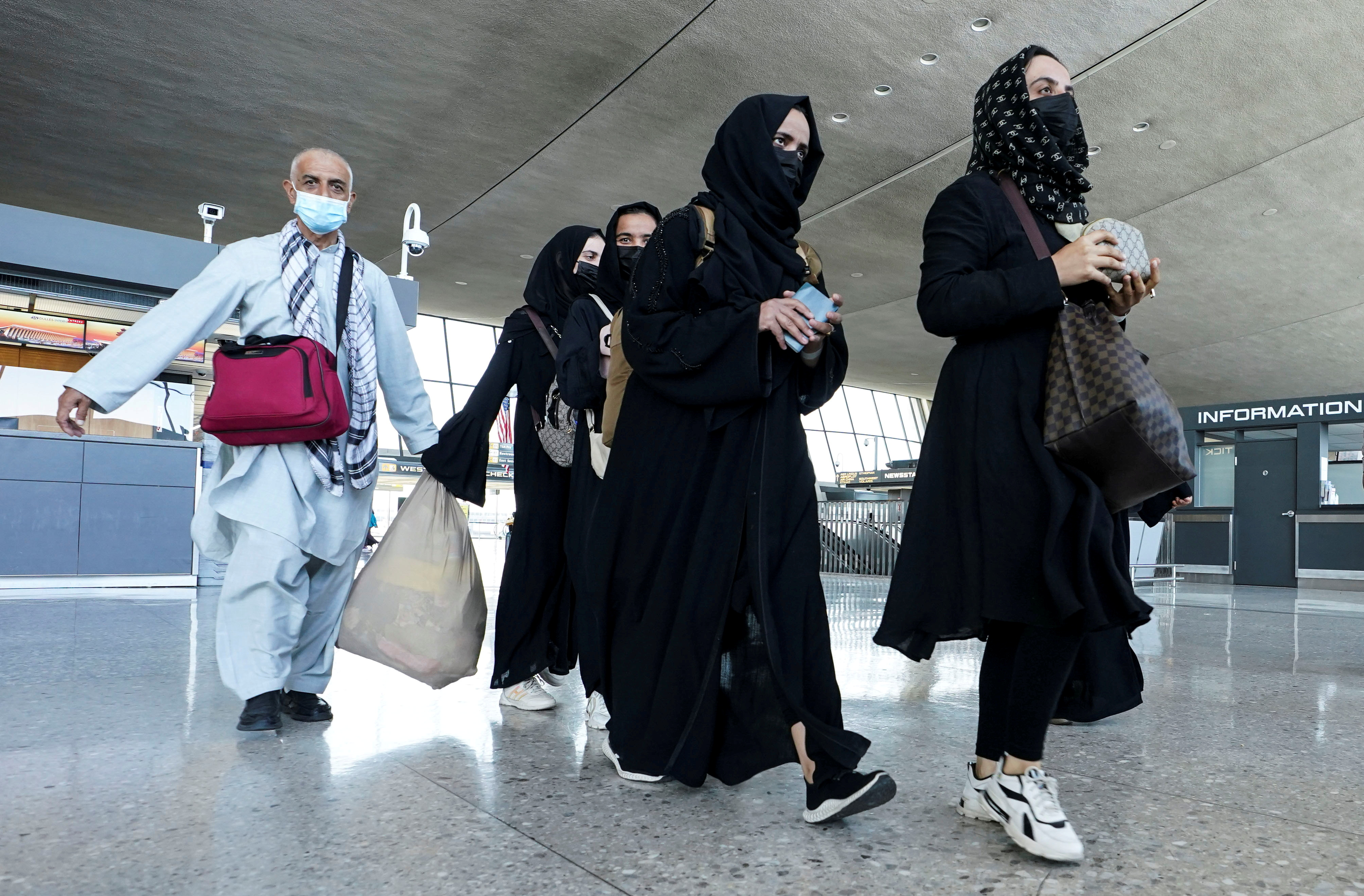 Afghan refugees walk to a bus taking them to a refugee processing center upon arrival at Dulles International Airport in Dulles, Virginia August 25, 2021. REUTERS/Kevin Lamarque
