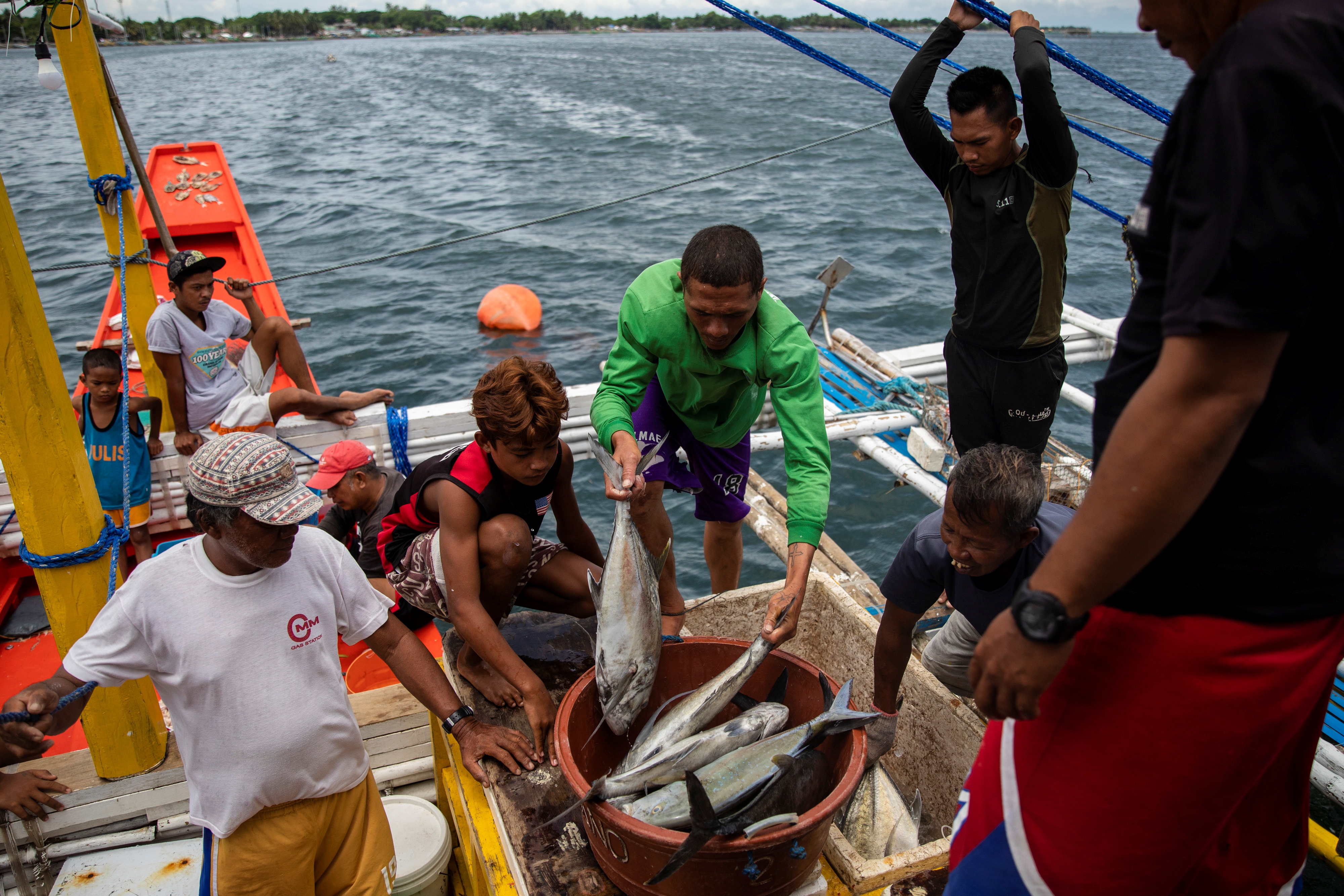 Filipino fishermen sort fish after arriving from a week-long trip to the disputed Scarborough Shoal, in Infanta, Pangasinan province, Philippines, July 6, 2021. REUTERS/Eloisa Lopez