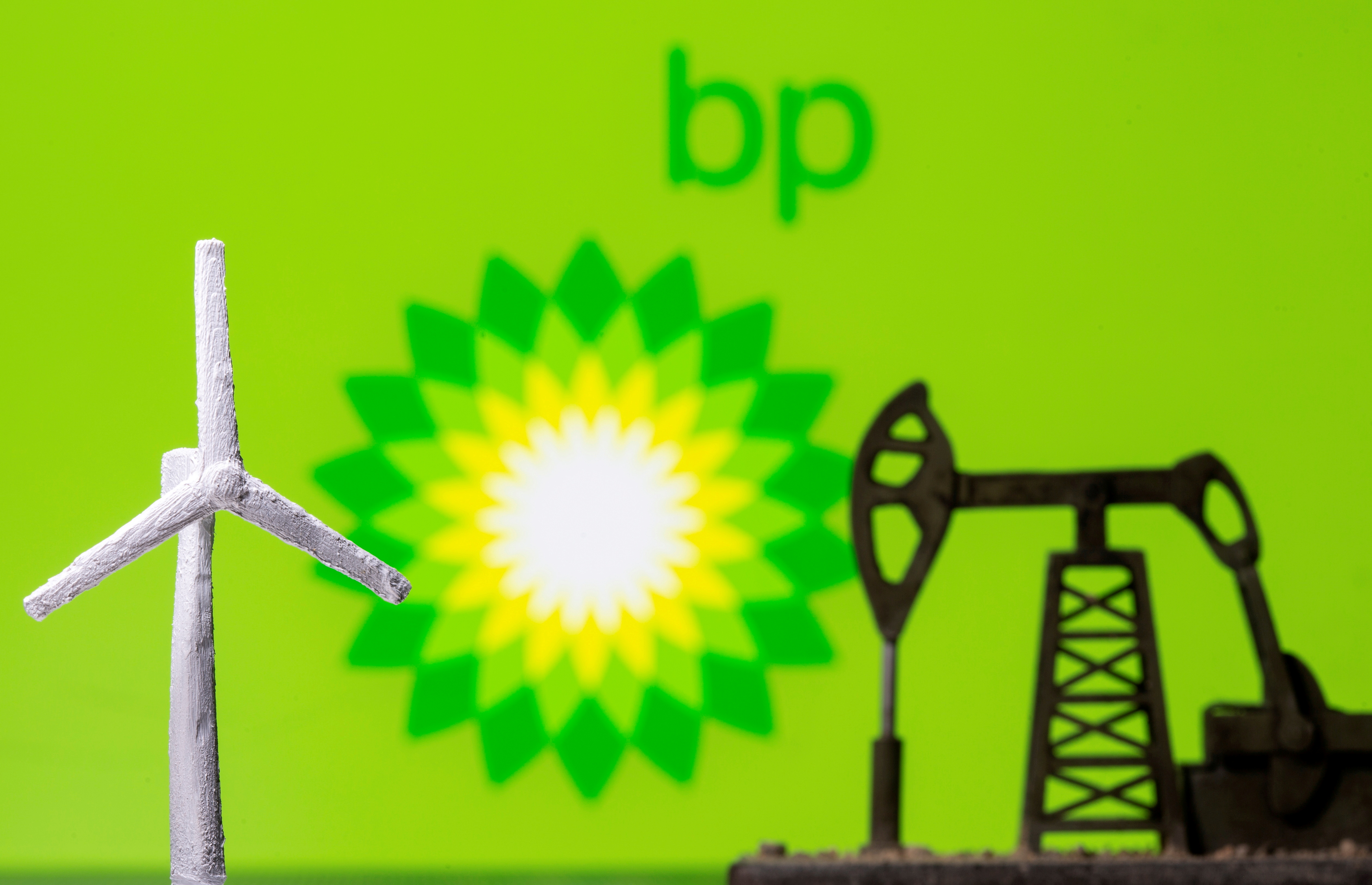 A 3D printed windmill and oil pump jack are seen in front of displayed BP logo in this illustration, August 11, 2021. REUTERS/Dado Ruvic
