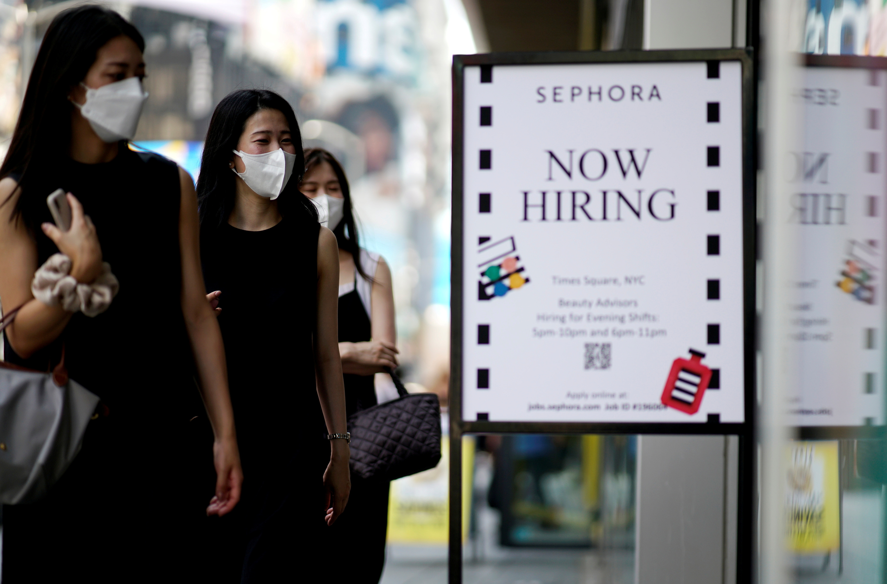 A sign advertising job openings is seen while people walk into the store in New York City, New York, U.S., August 6, 2021. REUTERS/Eduardo Munoz/File Photo
