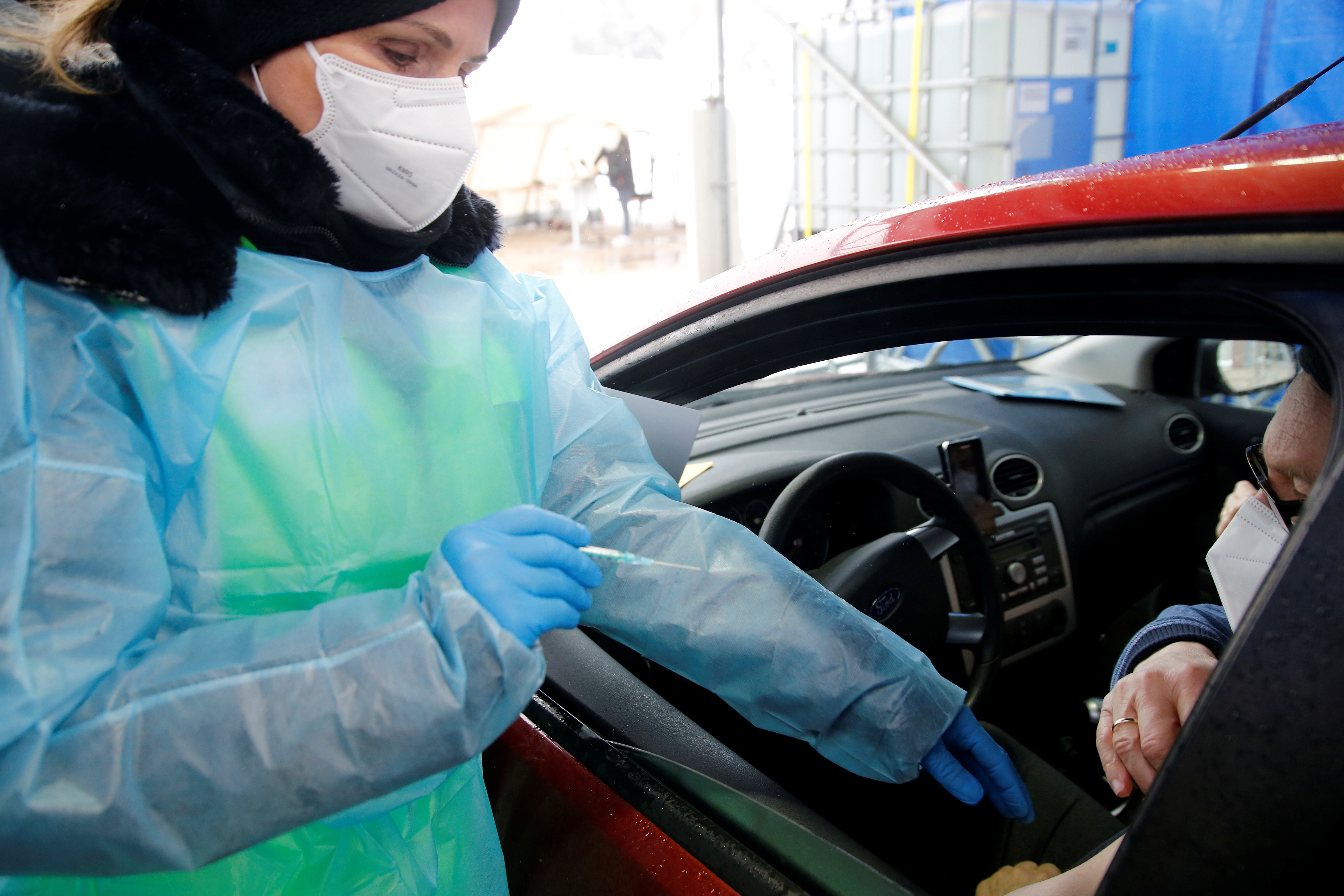 A medical employee vaccinates a man with the AstraZeneca COVID-19 vaccine at a drive-in vaccination center, as the spread of the coronavirus disease (COVID-19) continues, in Schwelm, Germany, April 7, 2021. REUTERS/Leon Kuegeler