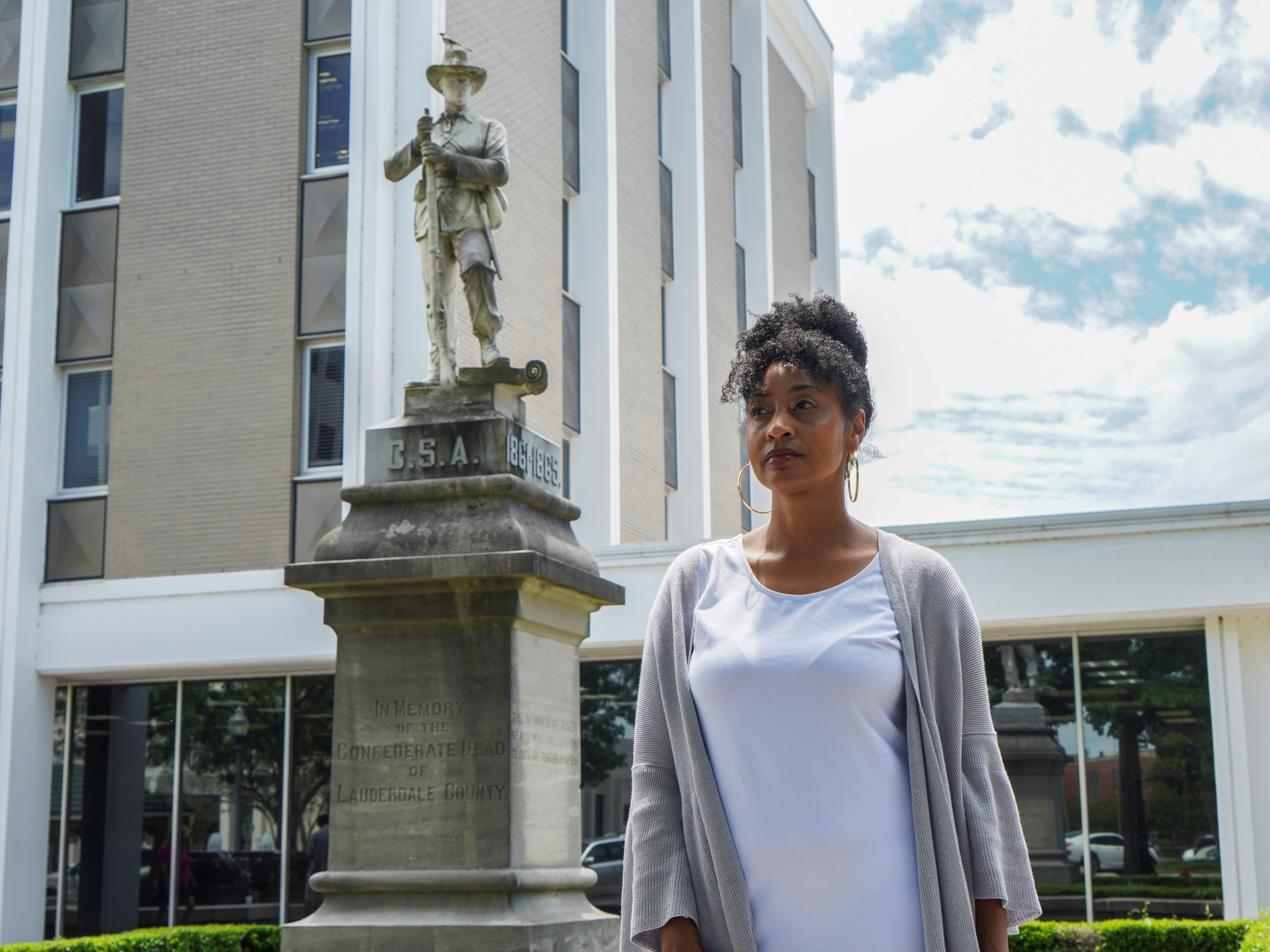 Camille Bennett poses for a photo in front of the confederate statue that she is trying to have moved to the confederate cemetery in Florence, Alabama, U.S., May 19, 2021.  REUTERS/Lawrence Bryant