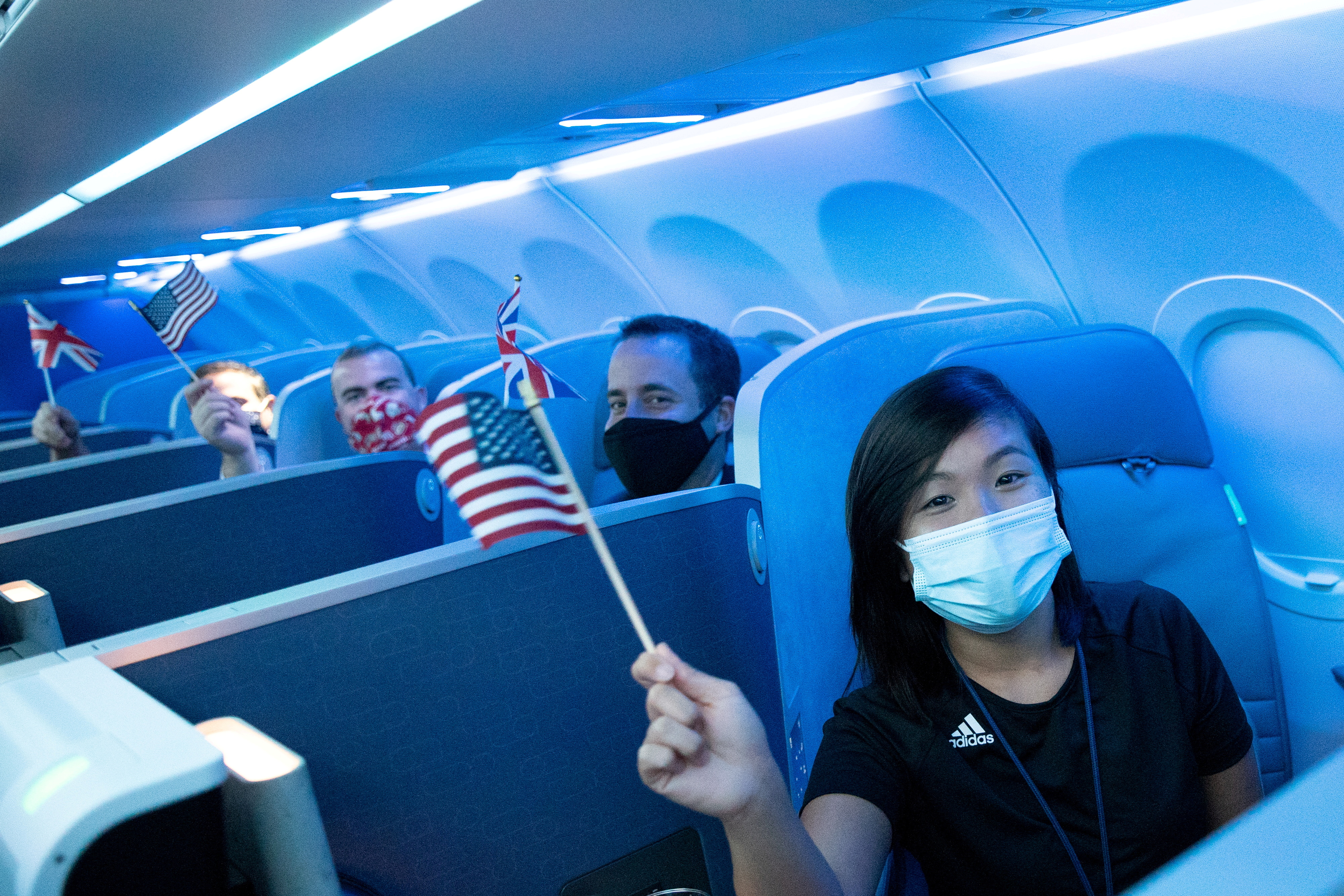 Passengers wearing protective masks hold American and British flags before a JetBlue flight to London at JFK International Airport in the Queens borough of New York City, New York, U.S., August 11, 2021. REUTERS/Jeenah Moon