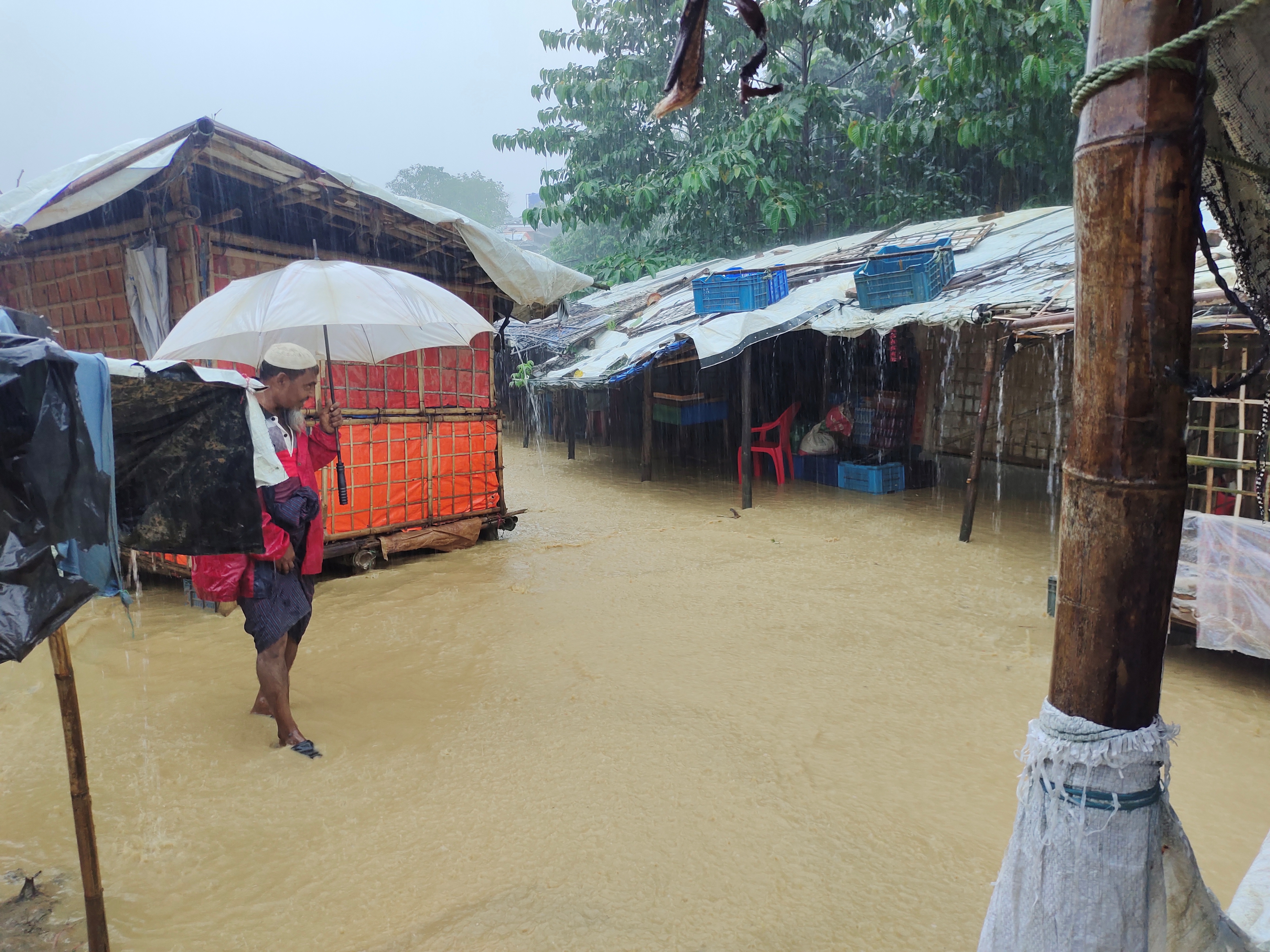 A man walks in a flooded street after heavy monsoon rains triggered flooding at Kutapalong refugee camp, in Cox's Bazar, Bangladesh July 27, 2021 in this picture obtained from social media. OMAR'S FILM SCHOOL/via REUTERS THIS IMAGE HAS BEEN SUPPLIED BY A THIRD PARTY. MANDATORY CREDIT. NO RESALES. NO ARCHIVES.