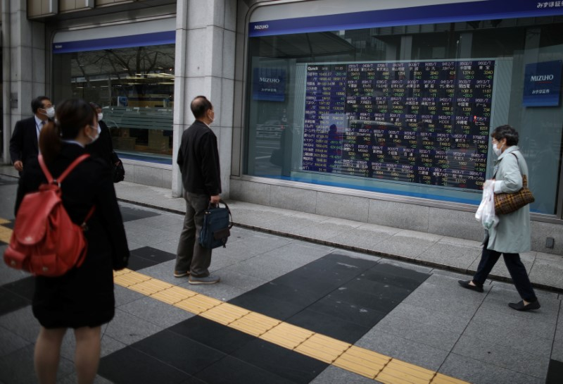 People wearing protective face masks, following an outbreak of the coronavirus disease (COVID-19), look at a stock quotation board outside a brokerage in Tokyo, Japan, March 10, 2020. REUTERS/Stoyan Nenov/Files