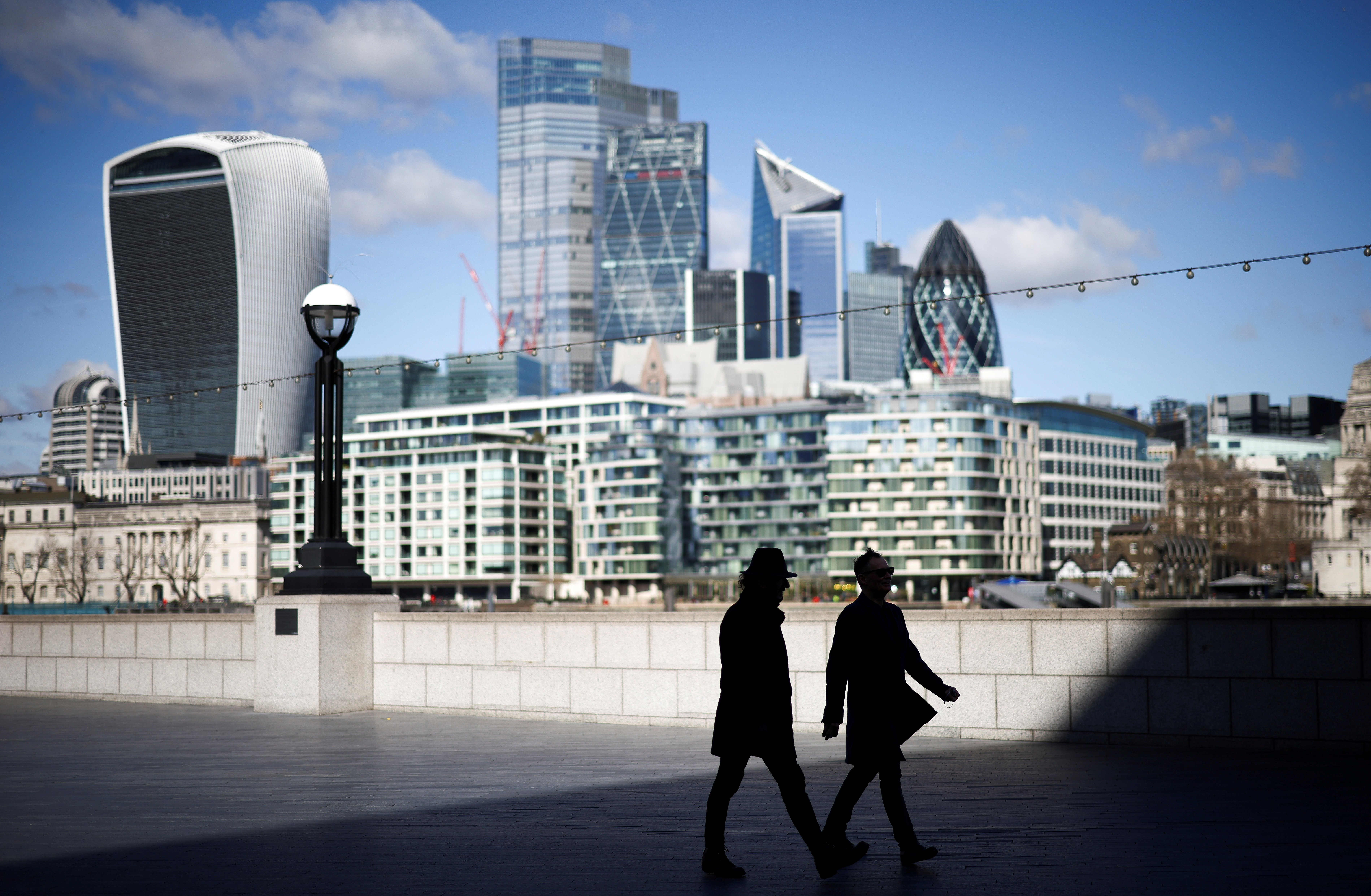 The City of London financial district can be seen as people walk along the south side of the River Thames, amid the coronavirus disease (COVID-19) outbreak in London, Britain, March 19, 2021. REUTERS/Henry Nicholls/File Photo