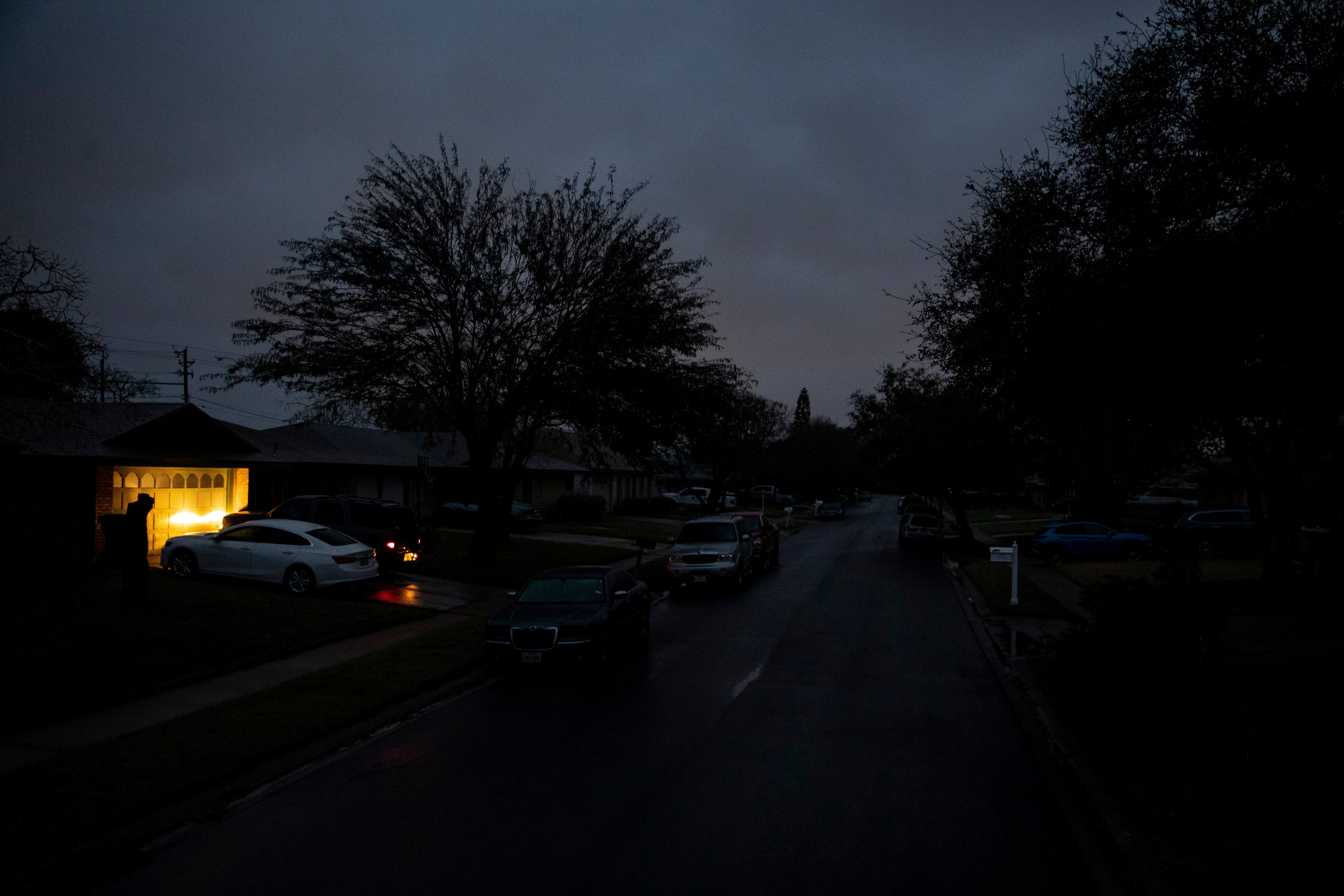 A car idles in a driveway on Jordan Drive, a street with no power in the early morning in Corpus Christi, Texas, U.S. February 17, 2021.  Courtney Sacco/Caller-Times/USA Today Network via REUTERS.