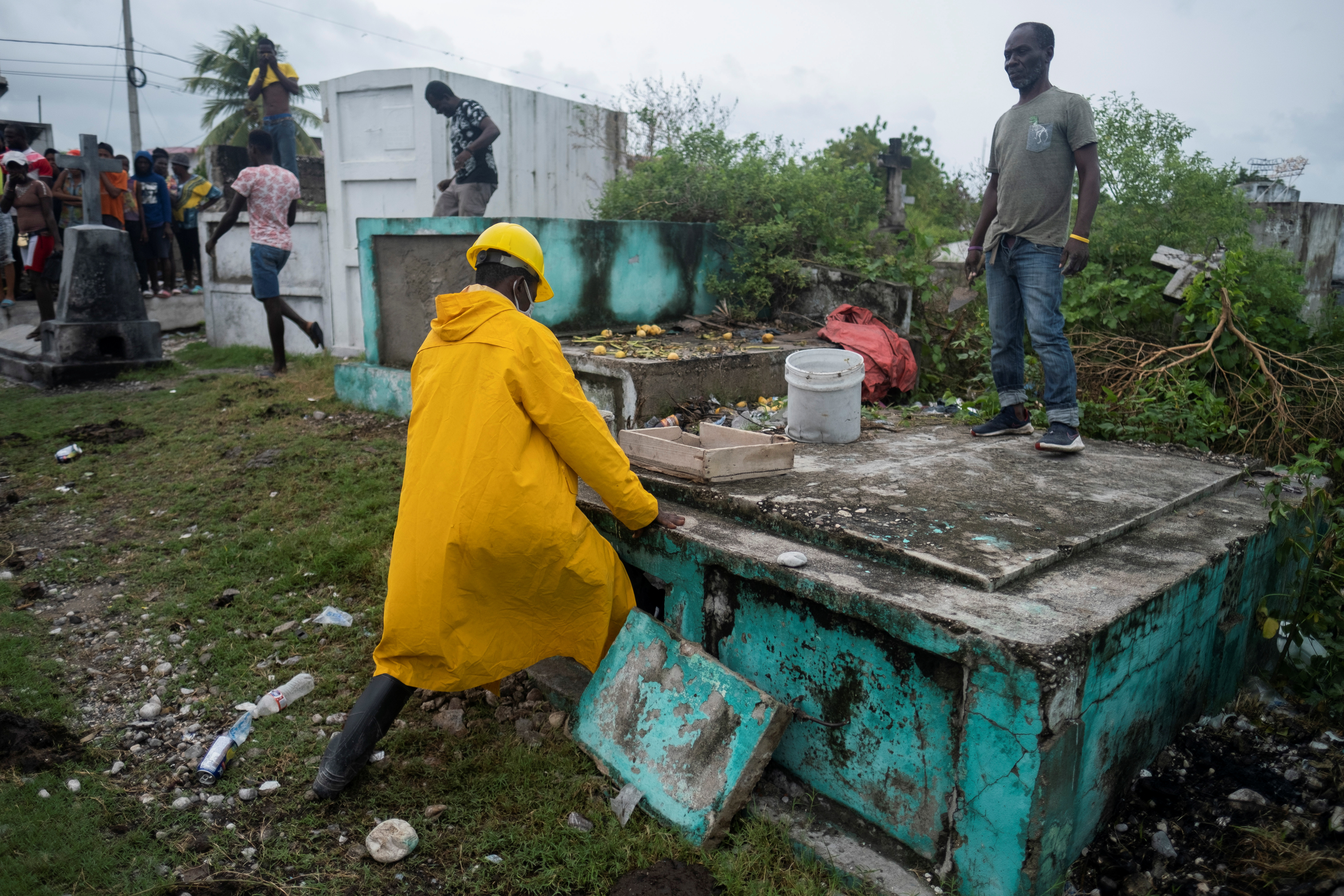 A man places the body of a victim of Saturday's 7.2 magnitude quake in a grave, in Les Cayes, Haiti August 17, 2021. REUTERS/Ricardo Arduengo