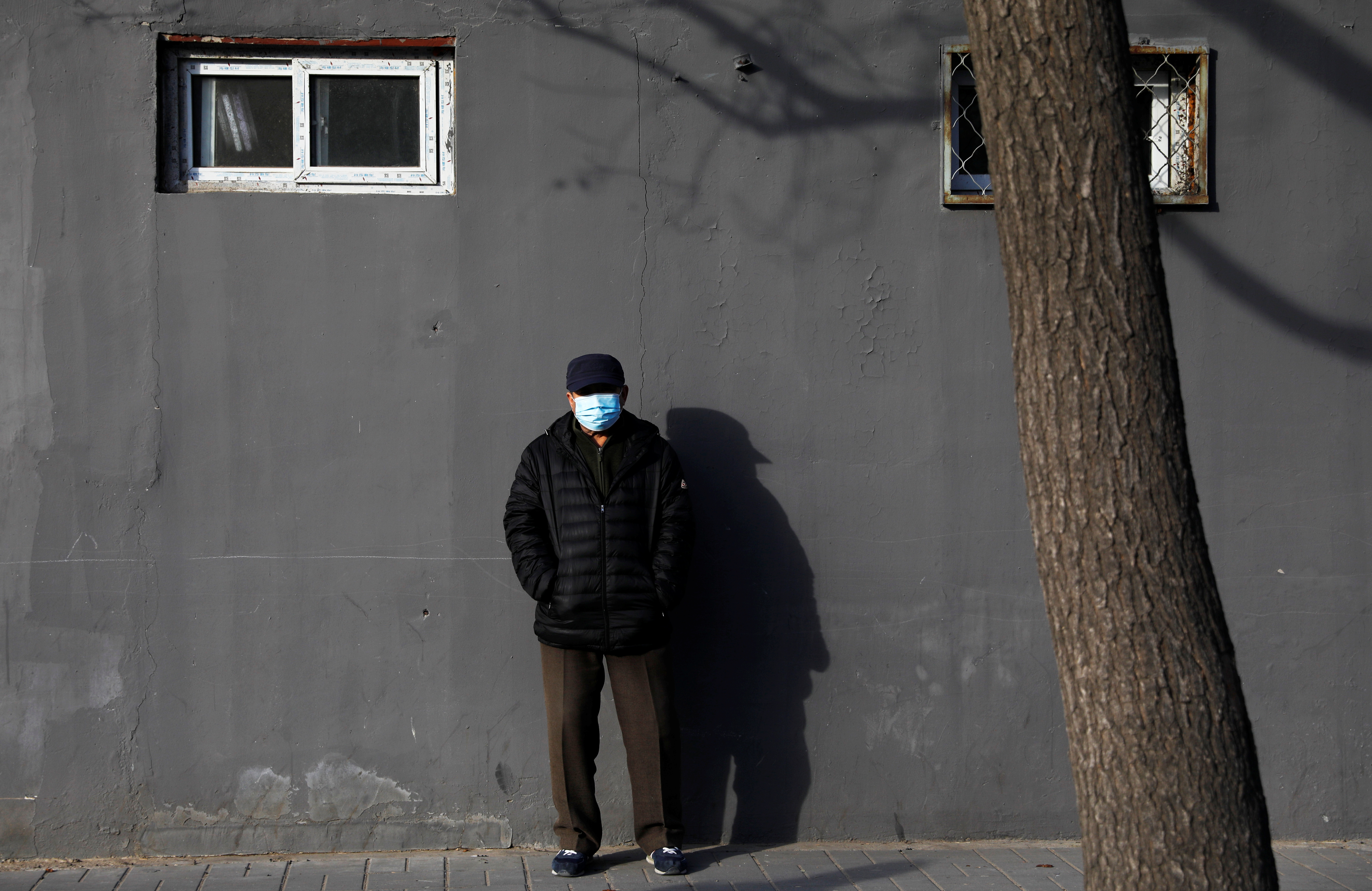 A man wearing a face mask stands along a street, following new cases of the coronavirus disease (COVID-19) in the country, in Beijing, China January 11, 2021. REUTERS/Tingshu Wang