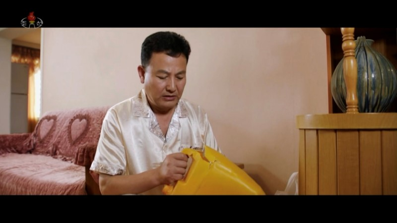 North Korean actor holds a plastic container in the movie