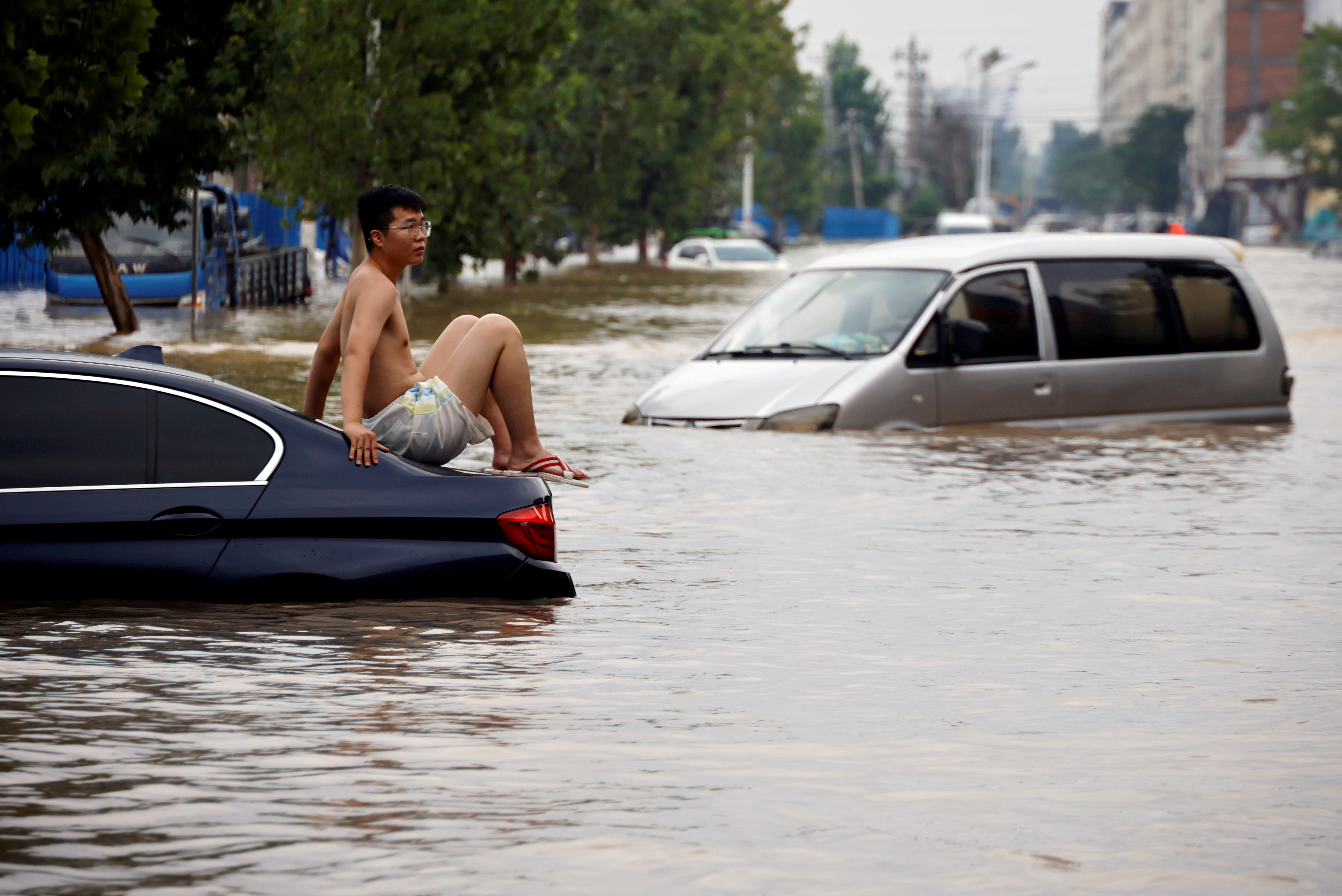 A man sits on a stranded vehicle on a flooded road following heavy rainfall in Zhengzhou, Henan province, China July 22, 2021.  REUTERS/Aly Song/File Photo