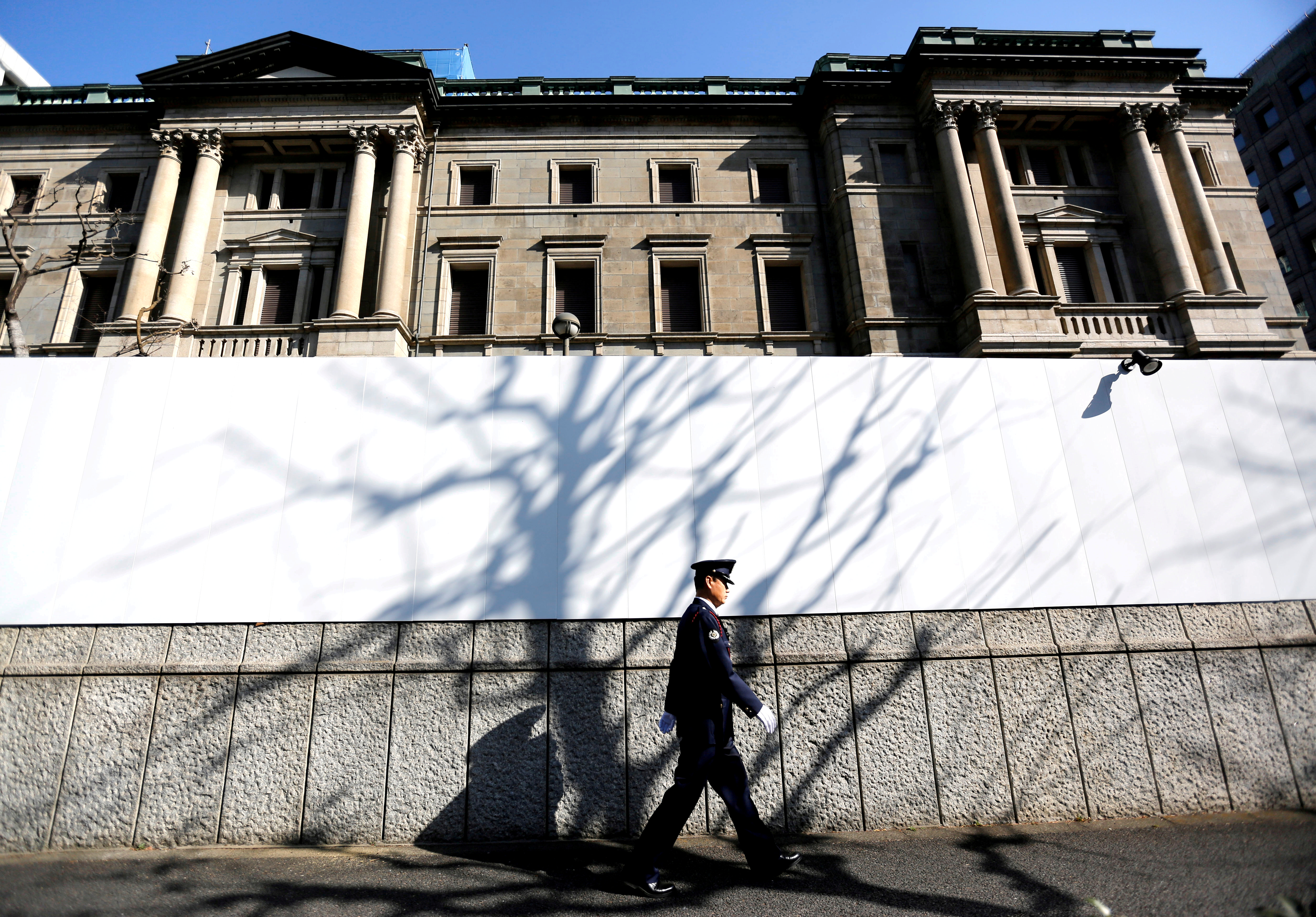 A security guard walks past in front of the Bank of Japan headquarters in Tokyo, Japan January 23, 2019. REUTERS/Issei Kato