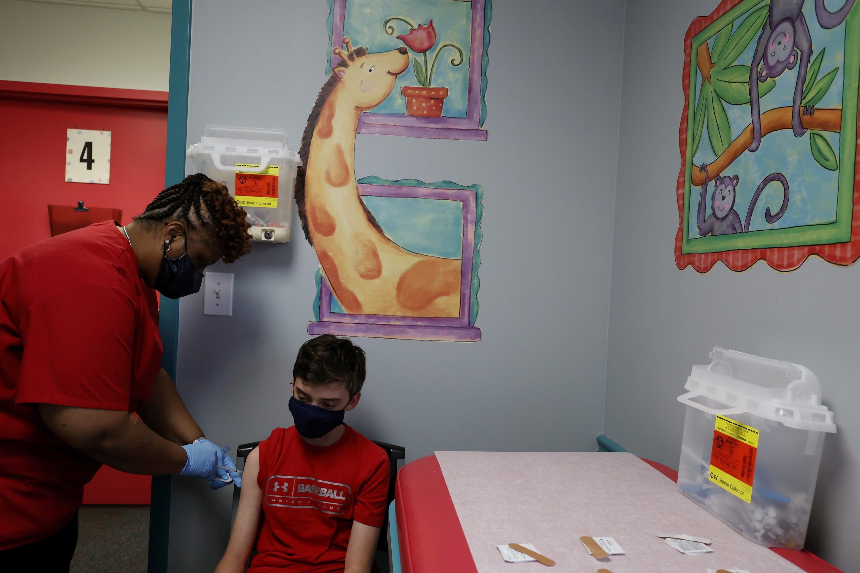 Aidan Mohl, 13, is inoculated with Pfizer's vaccine by Registered Medical Assistant Melissa Dalton at Dekalb Pediatric Center in Decatur, Georgia, May 11, 2021.  REUTERS/Chris Aluka Berry/File Photo