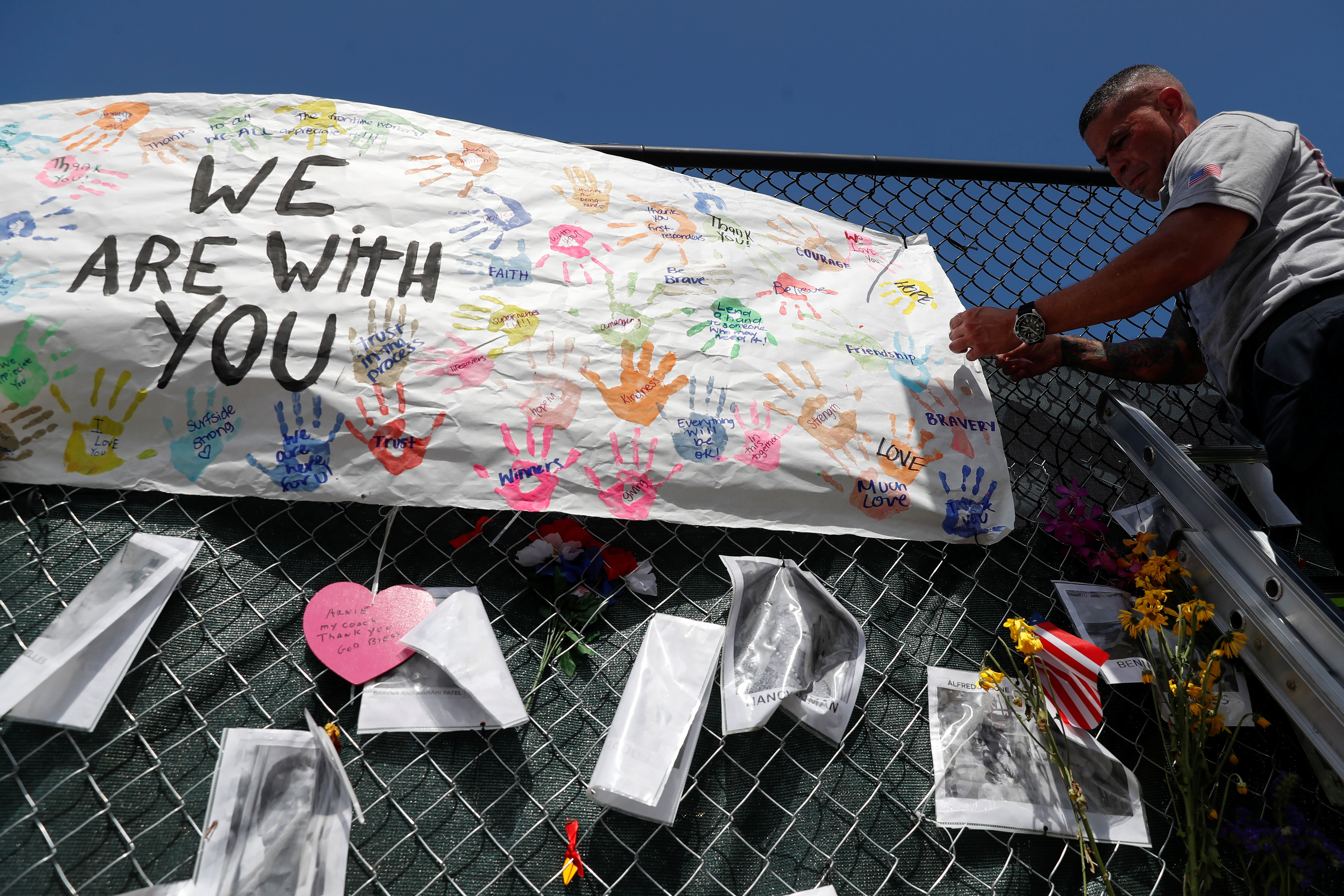 A member of the Miami-Dade Fire Rescue unit places a sign on a makeshift memorial for the victims of the Surfside's Champlain Towers South condominium collapse in Miami, Florida, U.S., July 8, 2021. REUTERS/Shannon Stapleton