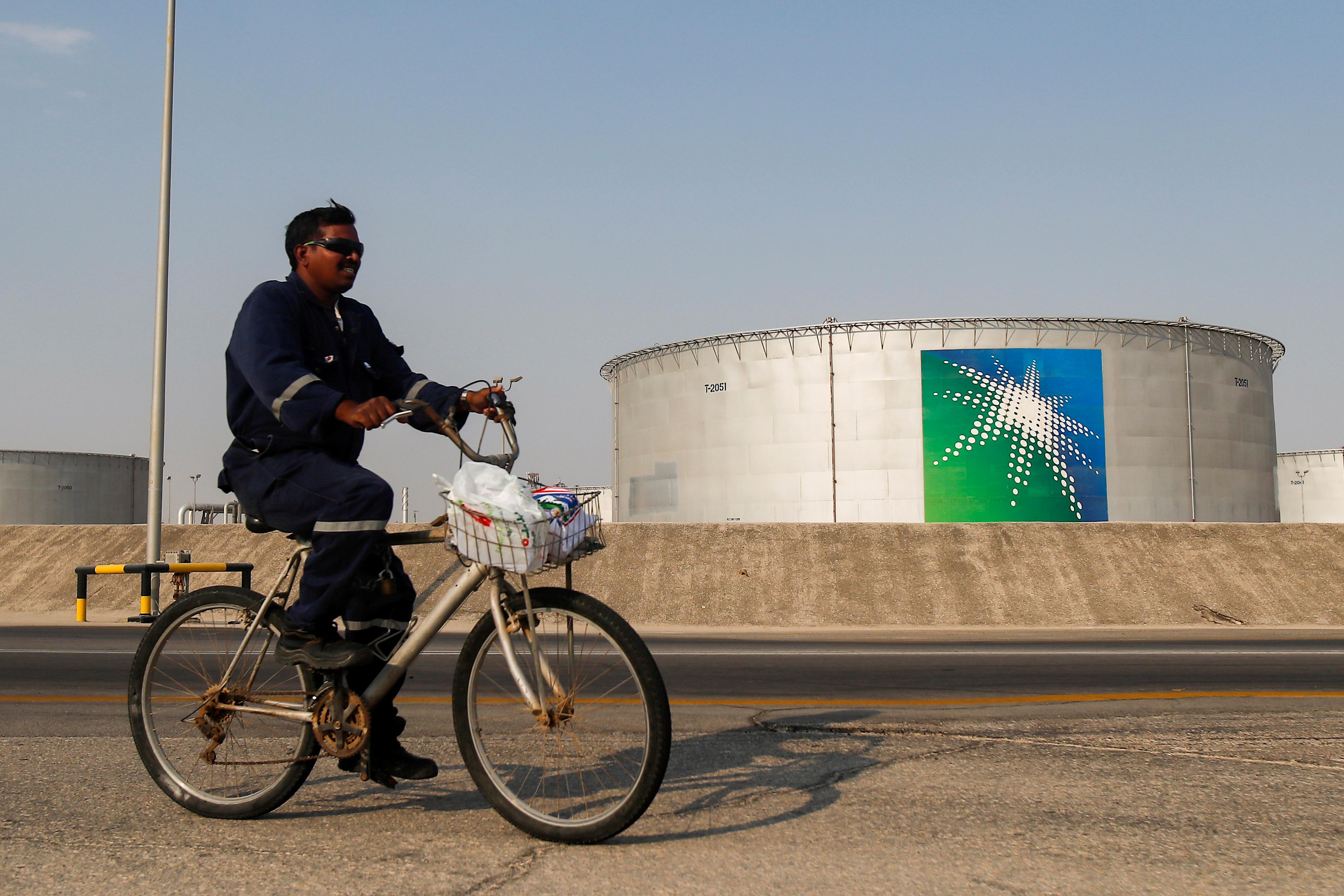 An employee rides a bicycle next to oil tanks at Saudi Aramco oil facility in Abqaiq, Saudi Arabia October 12, 2019. REUTERS/Maxim Shemetov