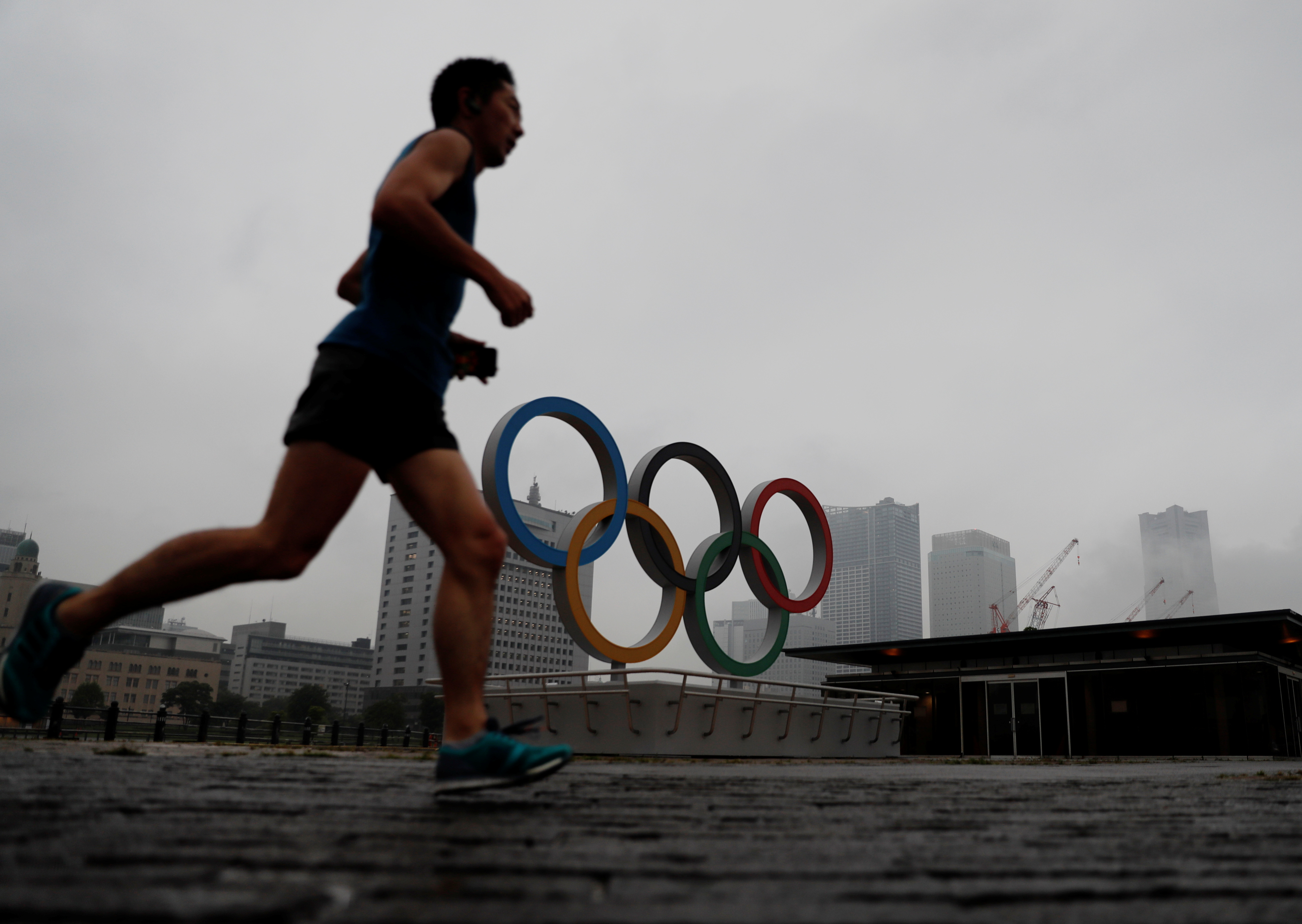 A jogger runs past a newly installed Olympic rings for celebrating the 2020 Tokyo Olympic Games in Yokohama, Japan, June 30, 2021.   REUTERS/Kim Kyung-Hoon