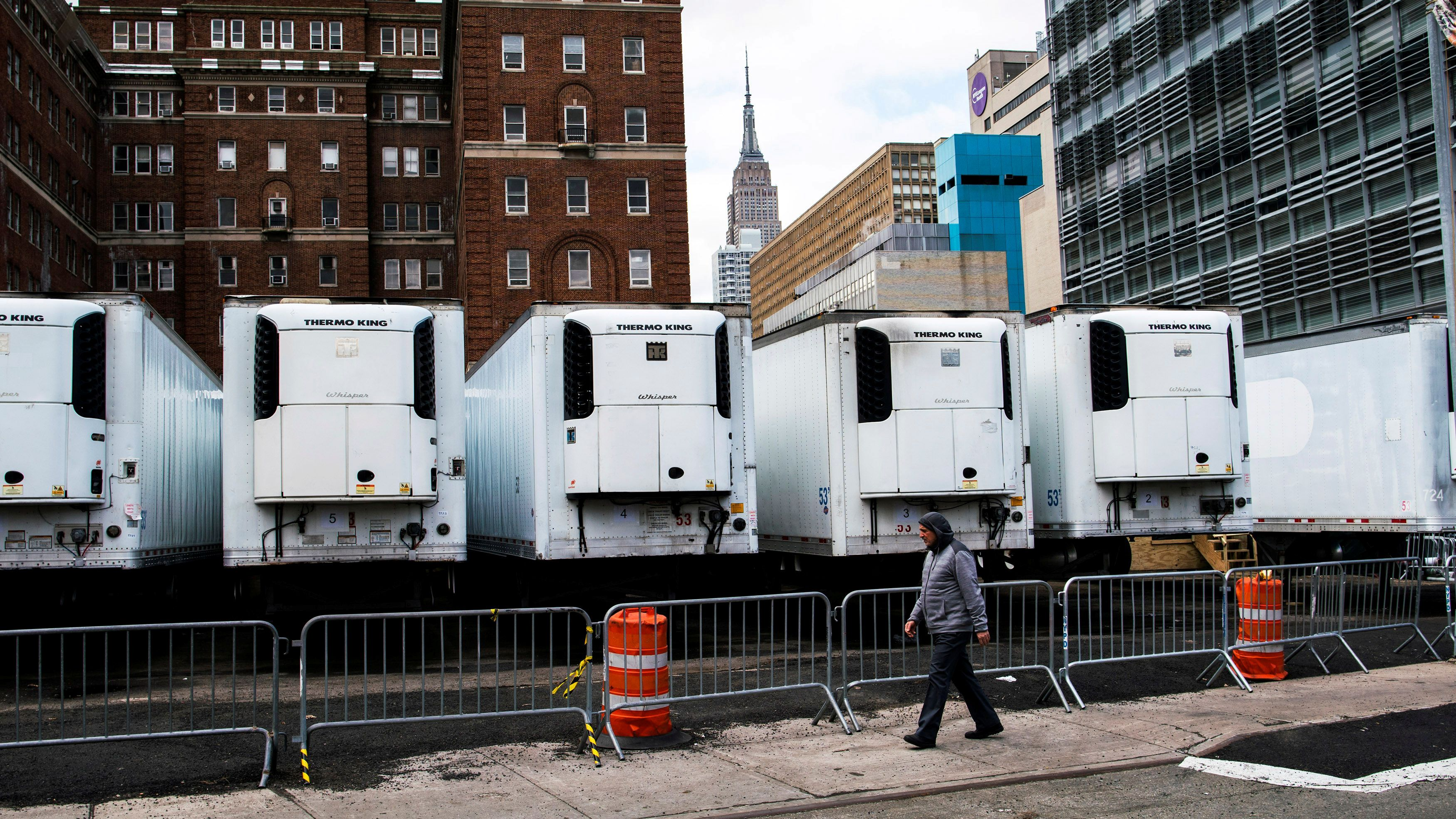 A man walks near a row of refrigeration units used as makeshift morgues located behind Bellevue Hospital as the Empire State Building is seen during the outbreak of the coronavirus disease (COVID-19) in New York City, U.S., March 31, 2020  REUTERS/Eduardo Munoz/File Photo