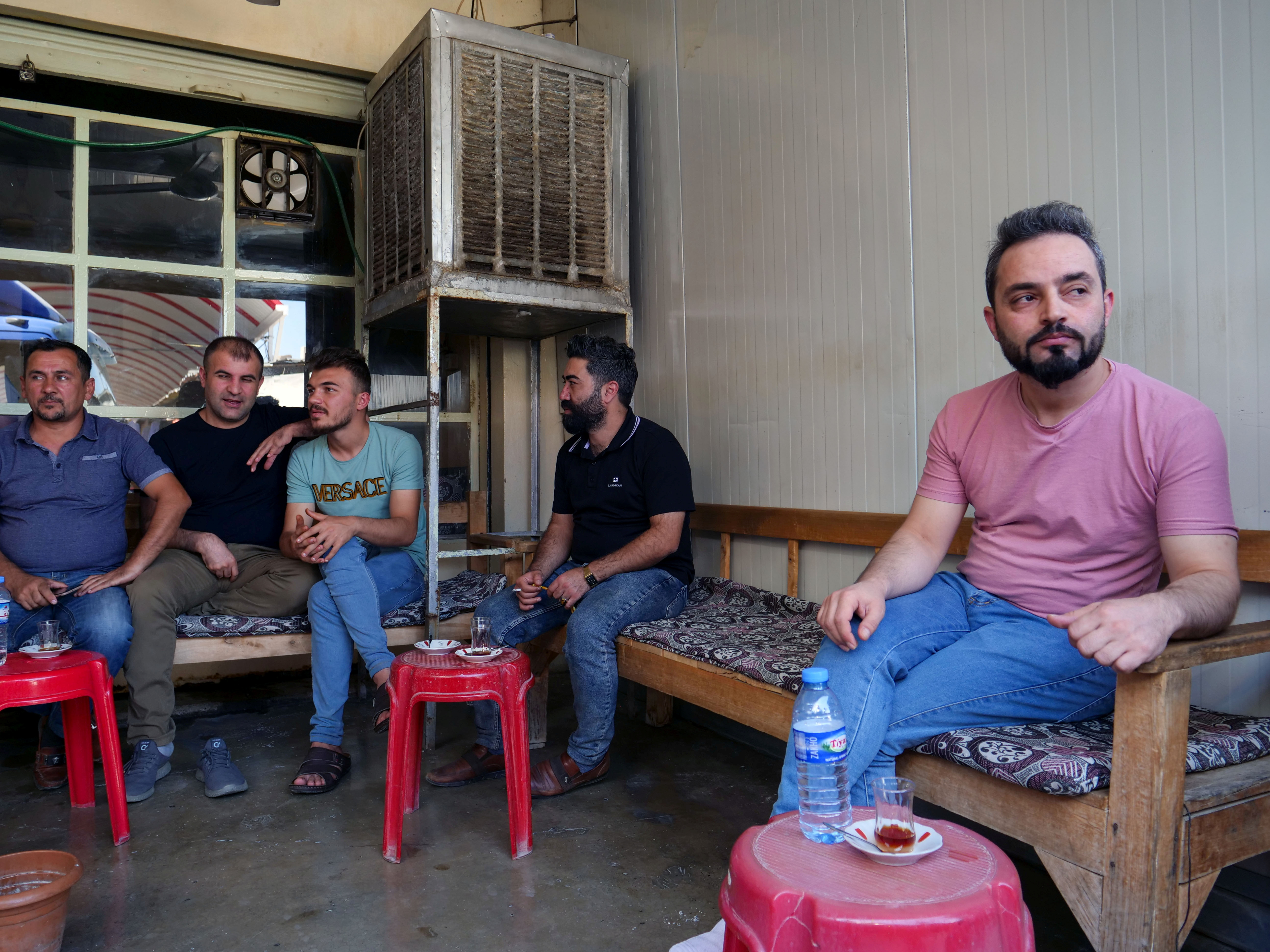 Abdullah Omar, a barber who has many relatives and friends who left to Belarus sits in a local tea shop in the town of Shiladze, Iraq September 22, 2021.  REUTERS/Charlotte Bruneau
