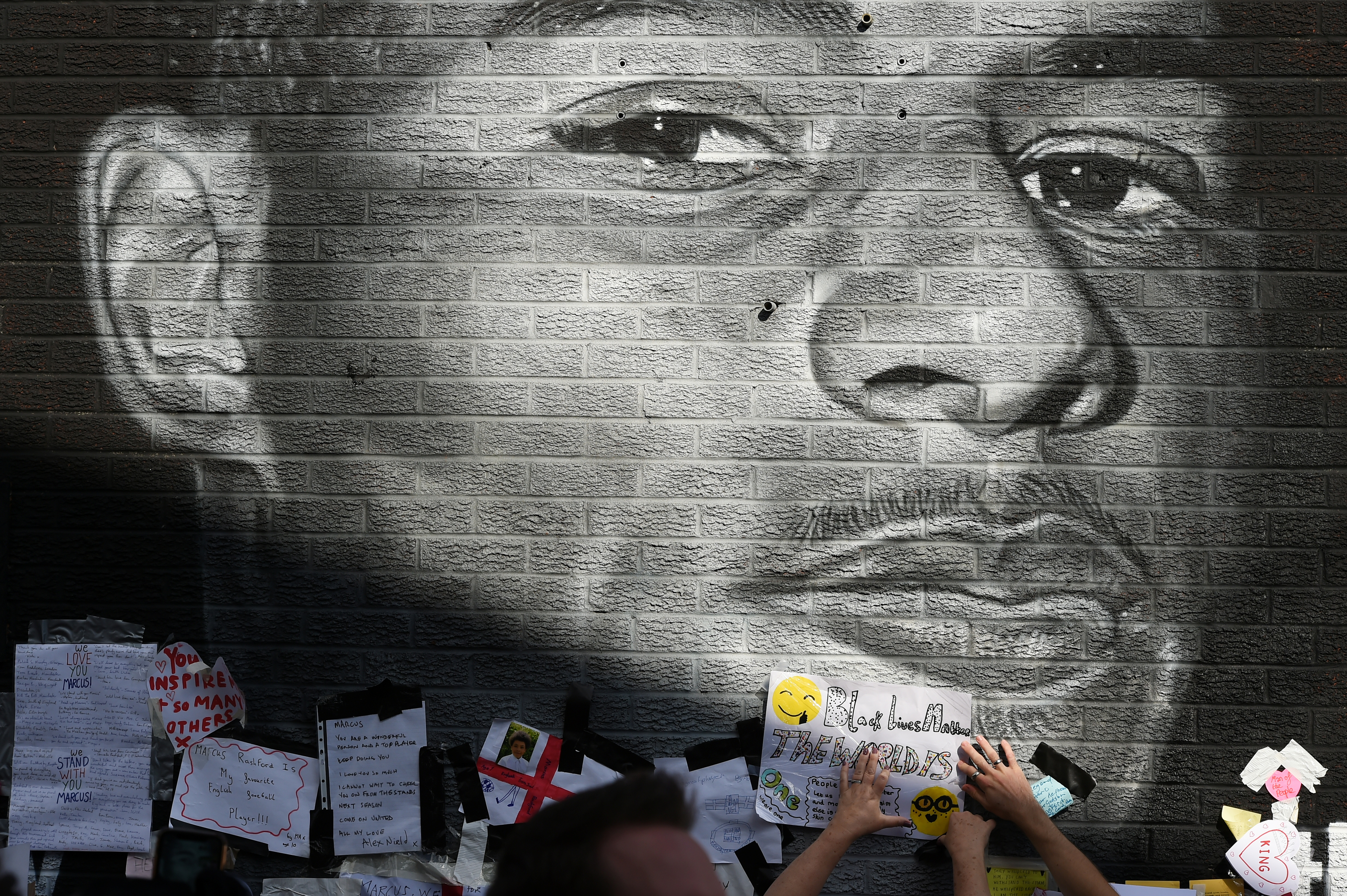 Stand Up to Racism Demonstration at the Marcus Rashford mural after it was defaced following the Euro 2020 Final between Italy and England - Withington, Manchester, Britain - July 13, 2021 People attach a message of support on the Marcus Rashford mural after it was defaced following the Euro 2020 Final between Italy and England REUTERS/Peter Powell/File Photo