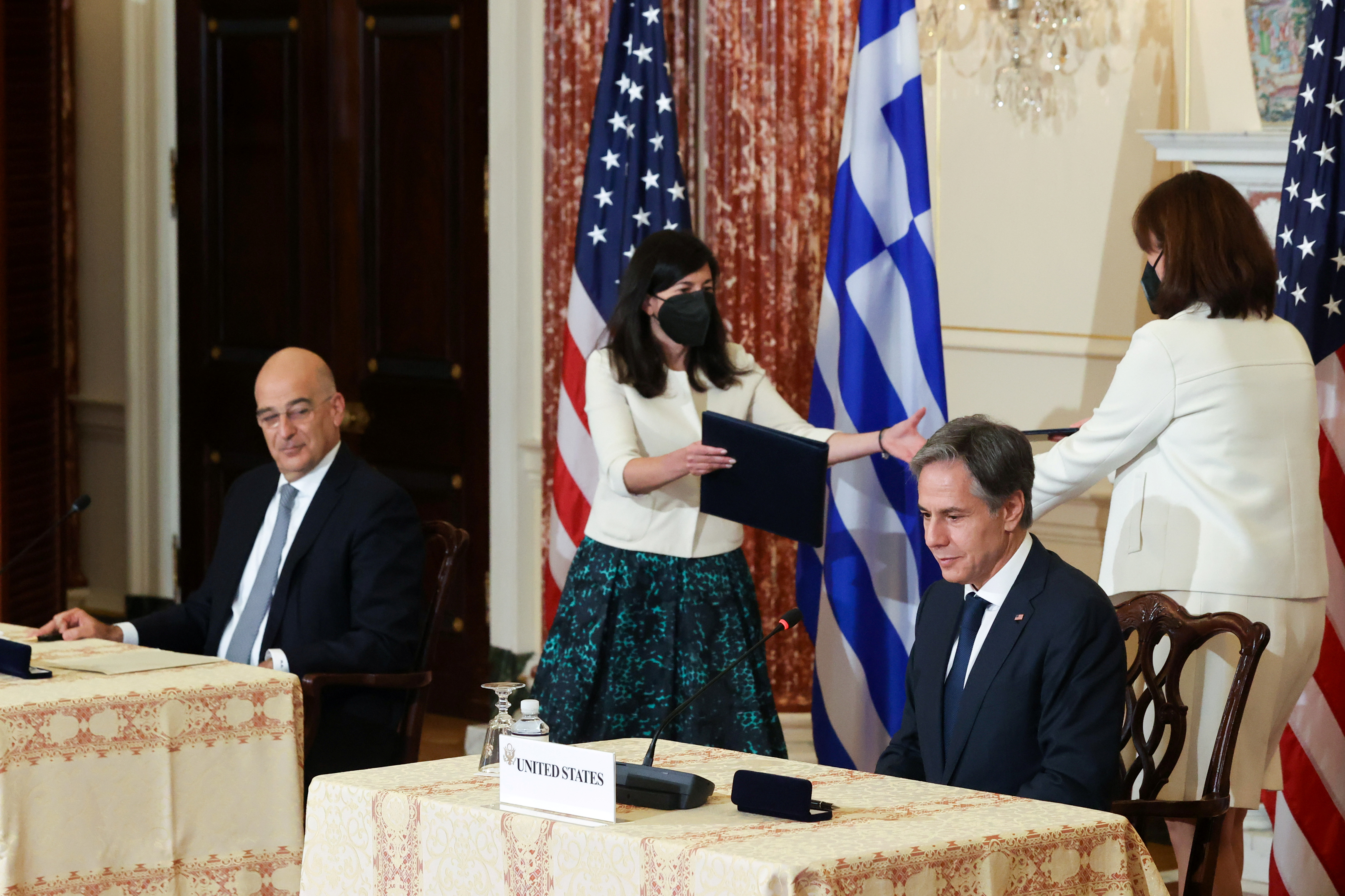 Aides exchange folios as U.S. Secretary of State Antony Blinken and Greece's Foreign Minister Nikos Dendias sign the renewal of the U.S.-Greece Mutual Defense Cooperation Agreement at the State Department in Washington, U.S. October 14, 2021.  REUTERS/Jonathan Ernst