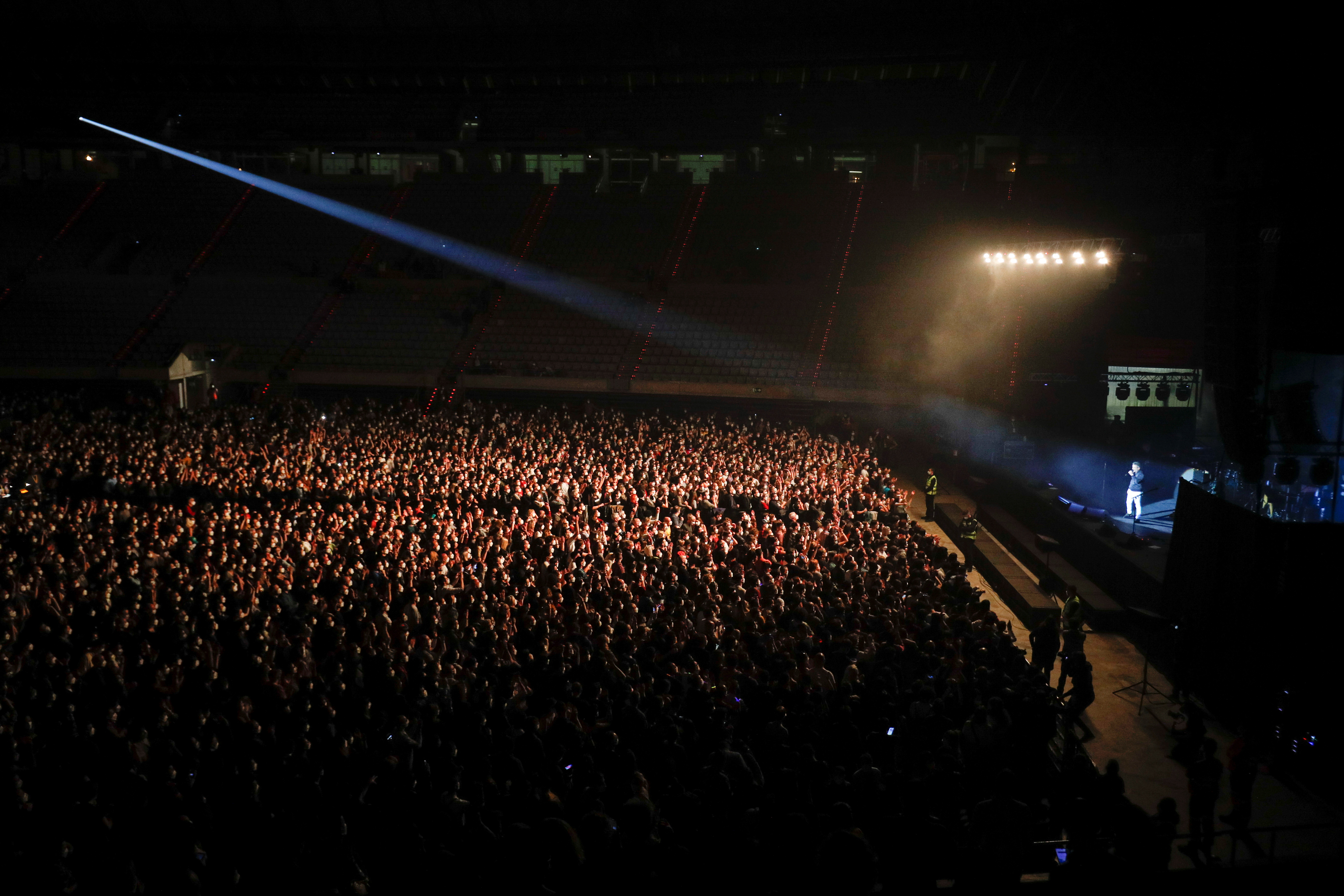 People wearing protective masks attend a concert of