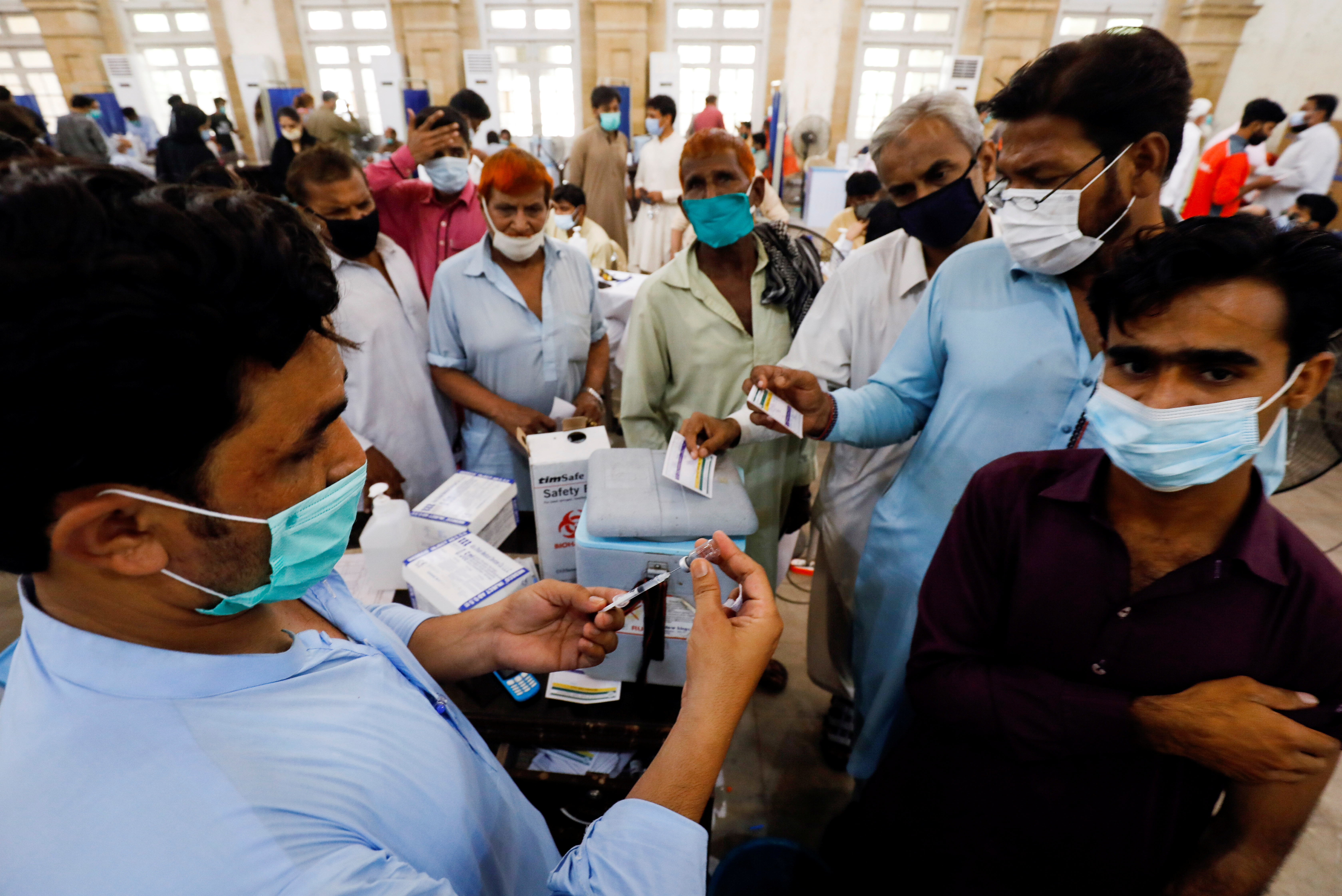 Residents with their registration cards gather at a counter to receive a dose of coronavirus disease (COVID-19) vaccine at a vaccination center in Karachi, Pakistan June 9, 2021. REUTERS/Akhtar Soomro