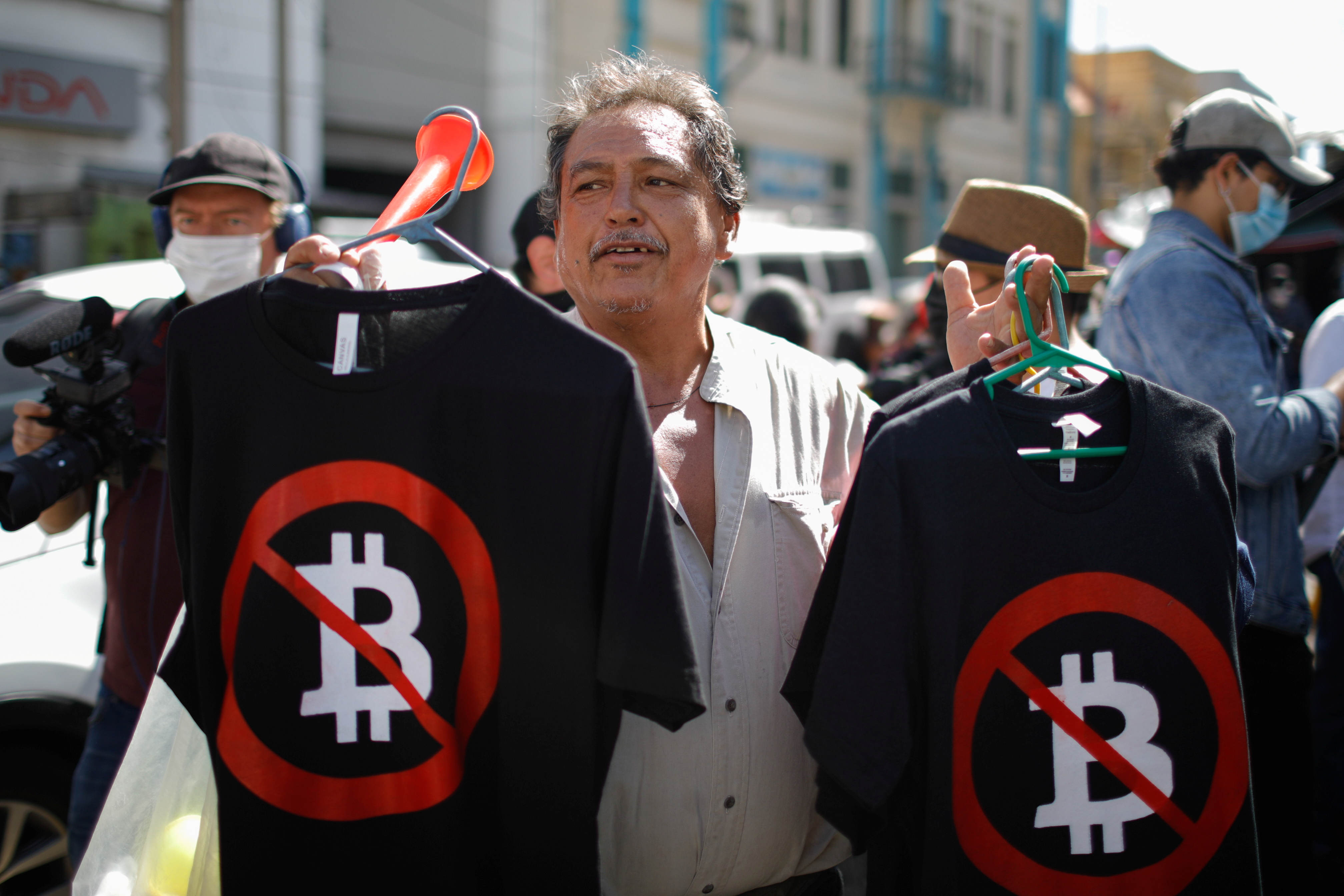 A man sells shirts as people participate in a protest against the use of Bitcoin as legal tender, in San Salvador, El Salvador, September 7, 2021. REUTERS/Jose Cabezas