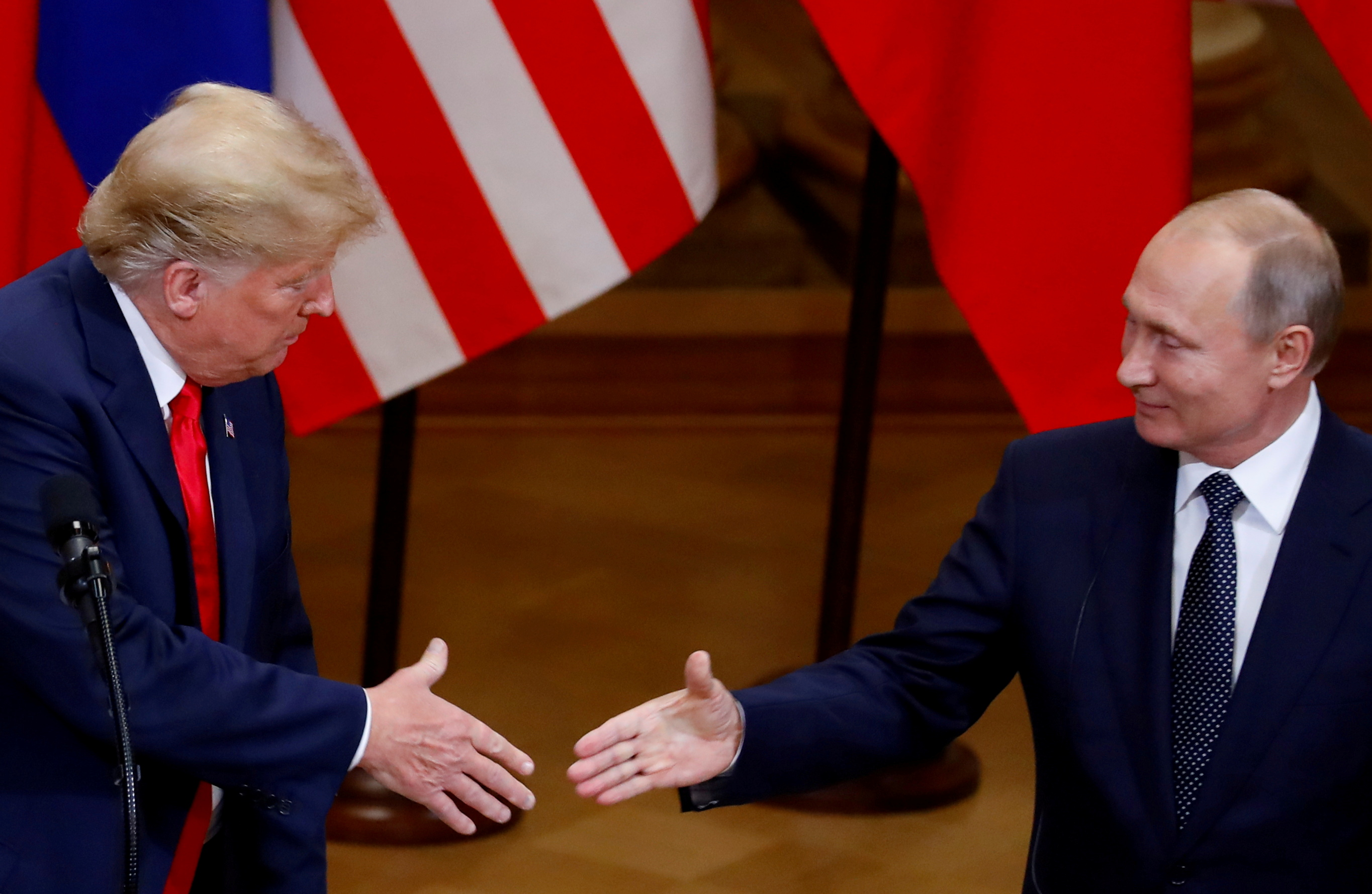 U.S. President Donald Trump and Russian President Vladimir Putin shake hands as they hold a joint news conference after their meeting in Helsinki, Finland, July 16, 2018. REUTERS/Leonhard Foeger/File Photo