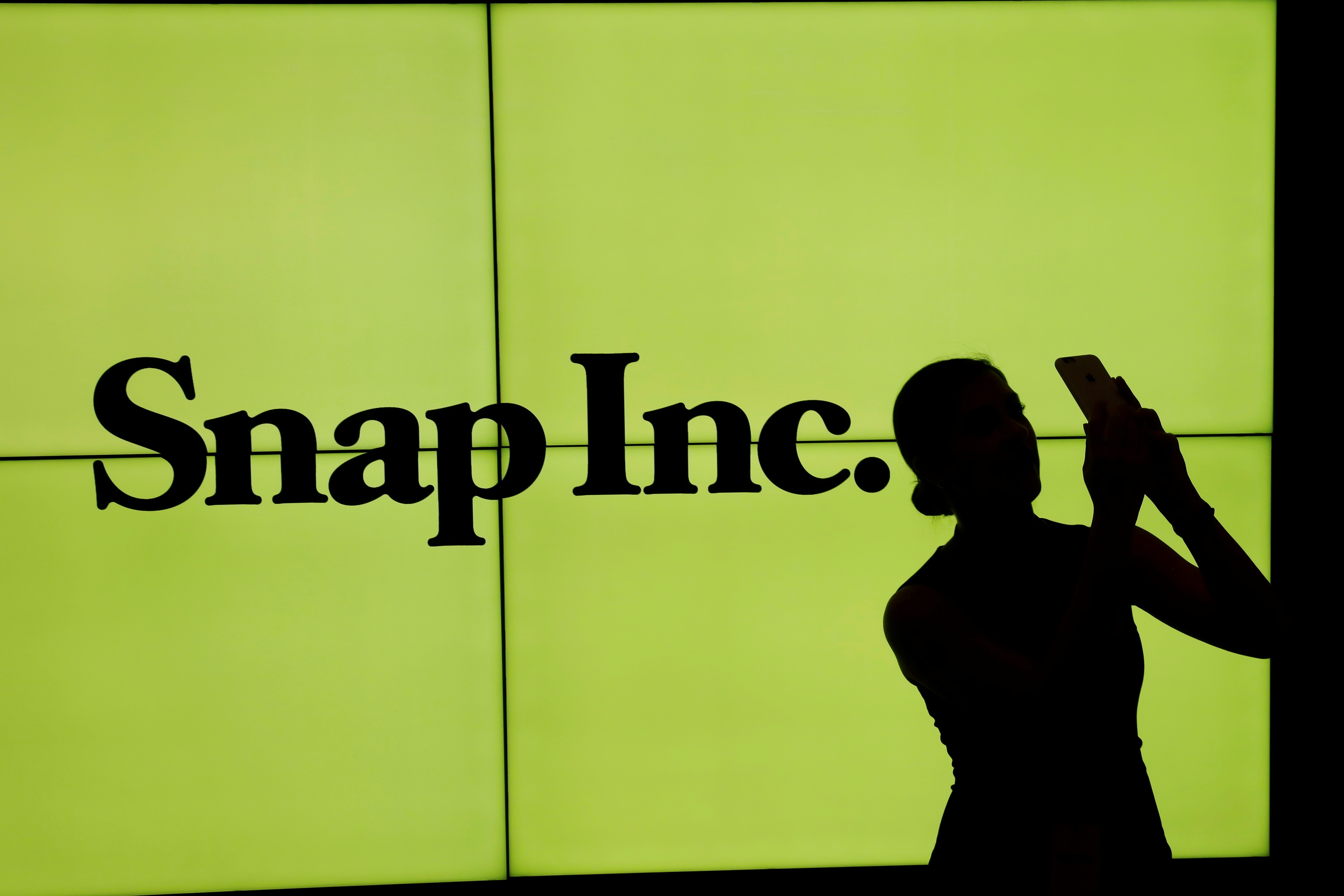 A woman stands in front of the logo of Snap Inc on the floor of the New York Stock Exchange (NYSE) in New York City, NY, U.S. March 2, 2017. REUTERS/Lucas Jackson/File Photo