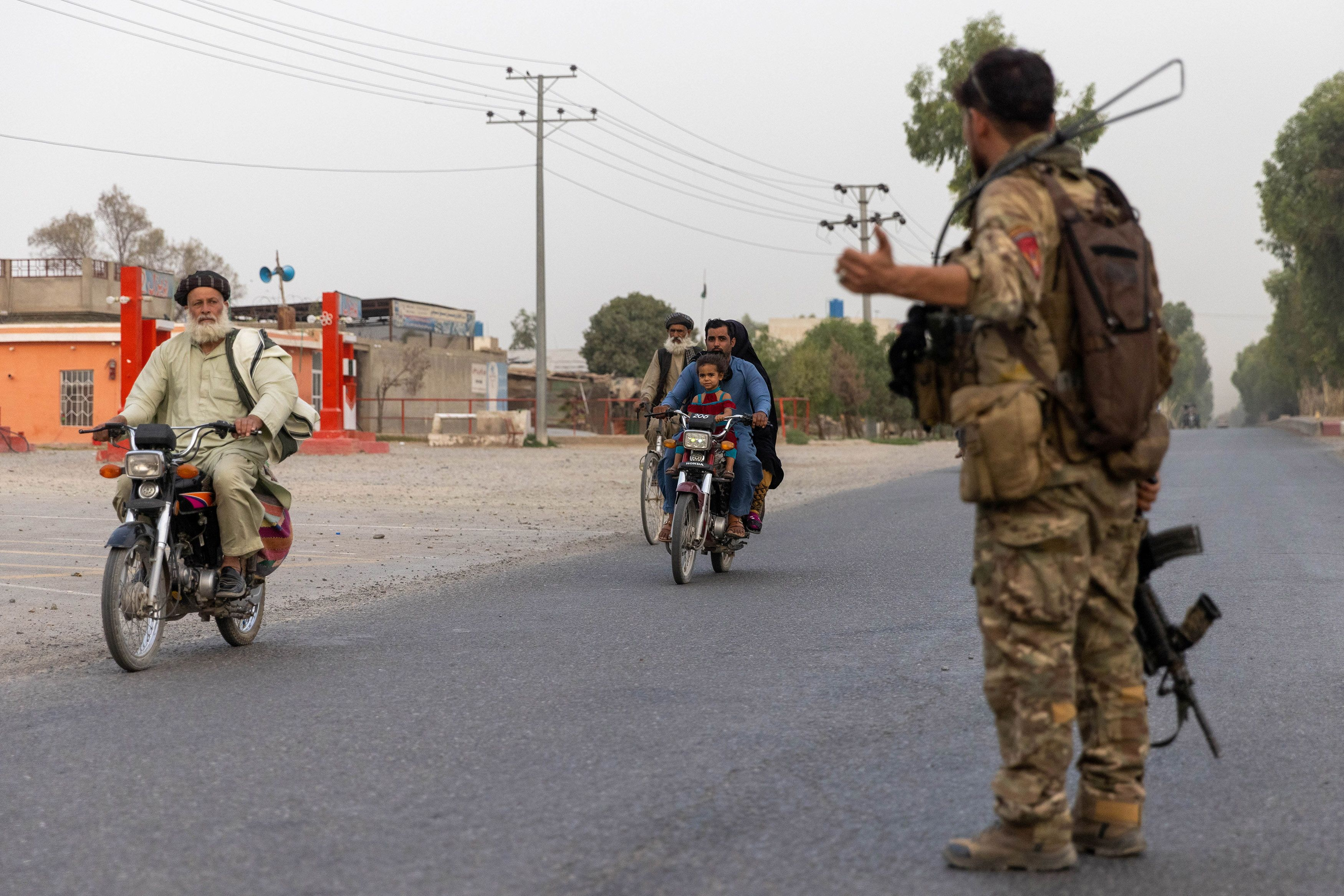 A member of the Afghan Special Forces directs traffic during the rescue mission of a policeman besieged at a check post surrounded by Taliban, in Kandahar province, Afghanistan, July 13, 2021. Picture taken July 13, 2021.REUTERS/Danish Siddiqui
