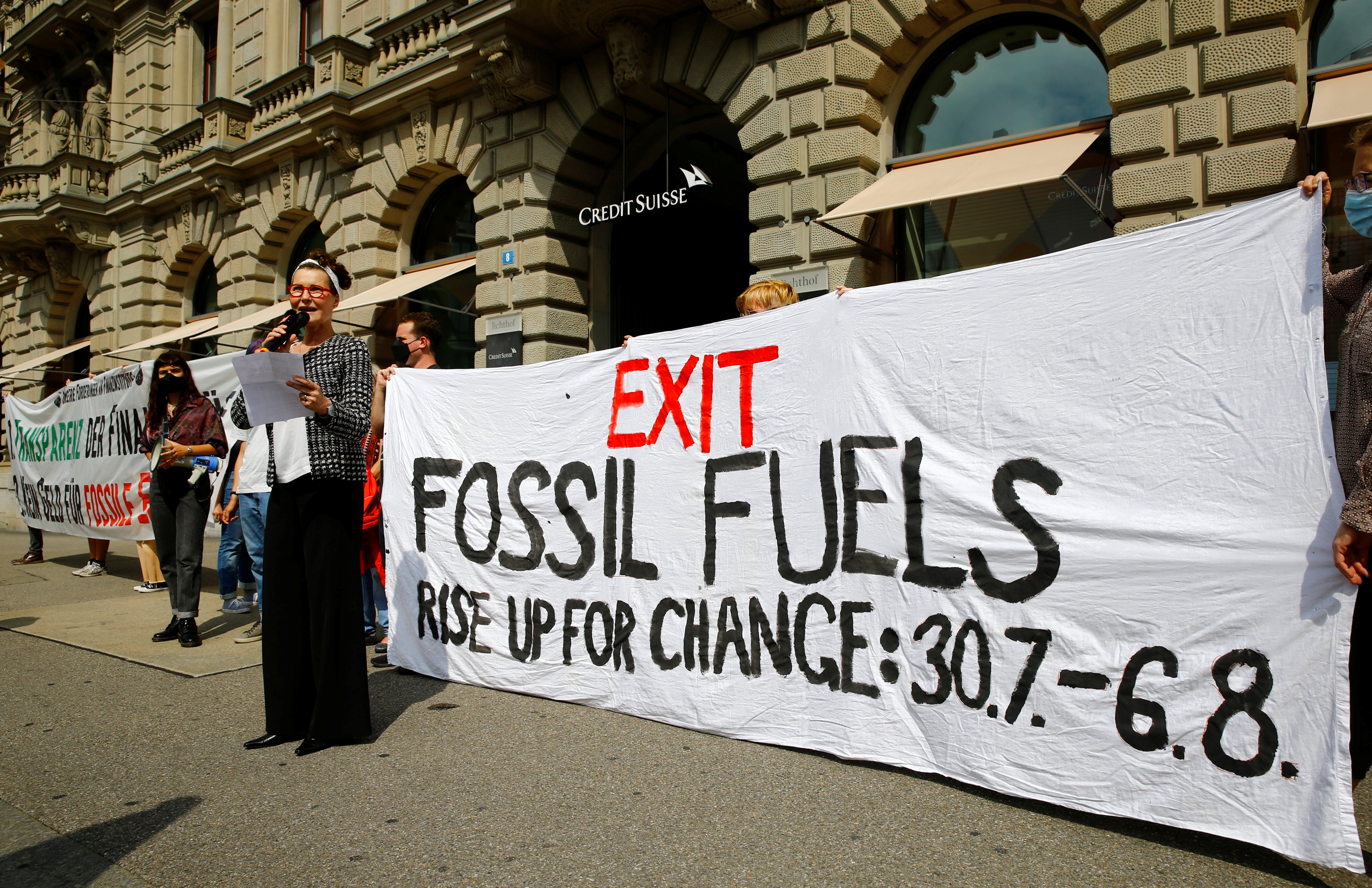 A woman, introduced as a representative of the Swiss bank Credit Suisse, speaks as climate activists of the 'Rise up for Change' coalition display a banner to protest in front of the bank's headquarters in Zurich, Switzerland, July 26, 2021. REUTERS/Arnd WIegmann