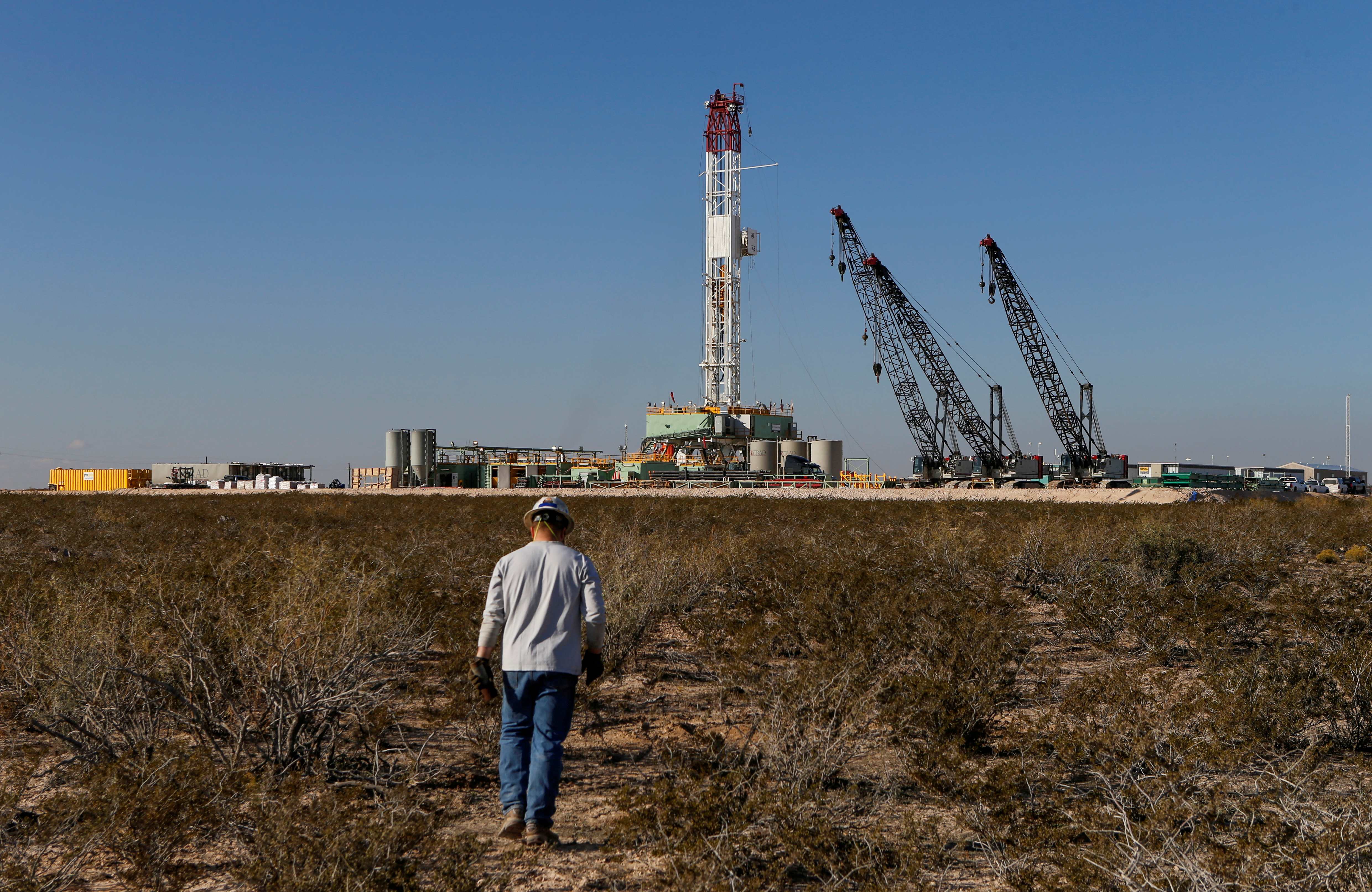 An oil worker walks toward a drill rig after placing ground monitoring equipment in the vicinity of the underground horizontal drill in Loving County, Texas, U.S., November 22, 2019. REUTERS/Angus Mordant/File Photo