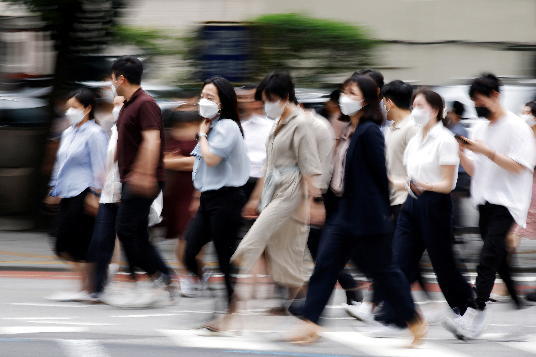 Commuters wearing masks to avoid contracting the coronavirus disease (COVID-19) walk on a zebra crossing in Seoul, South Korea, July 5, 2021.    REUTERS/Kim Hong-Ji