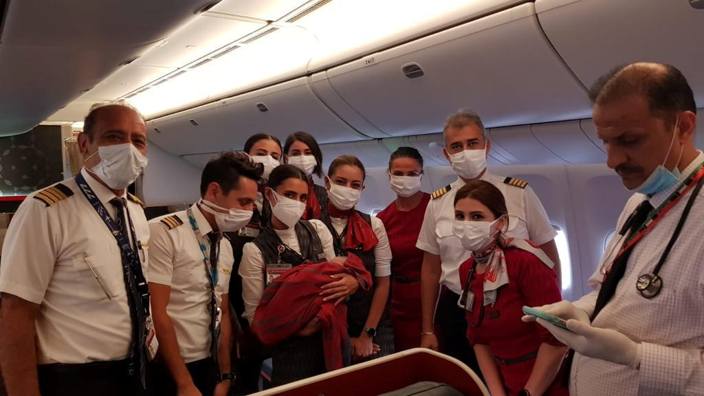 Turkish Airlines cabin crew members pose with the newborn Afghan baby girl named Havva on board an evacuation flight from Dubai to Britain's Birmingham, August 28, 2021. Turkish Airlines/Handout via REUTERS