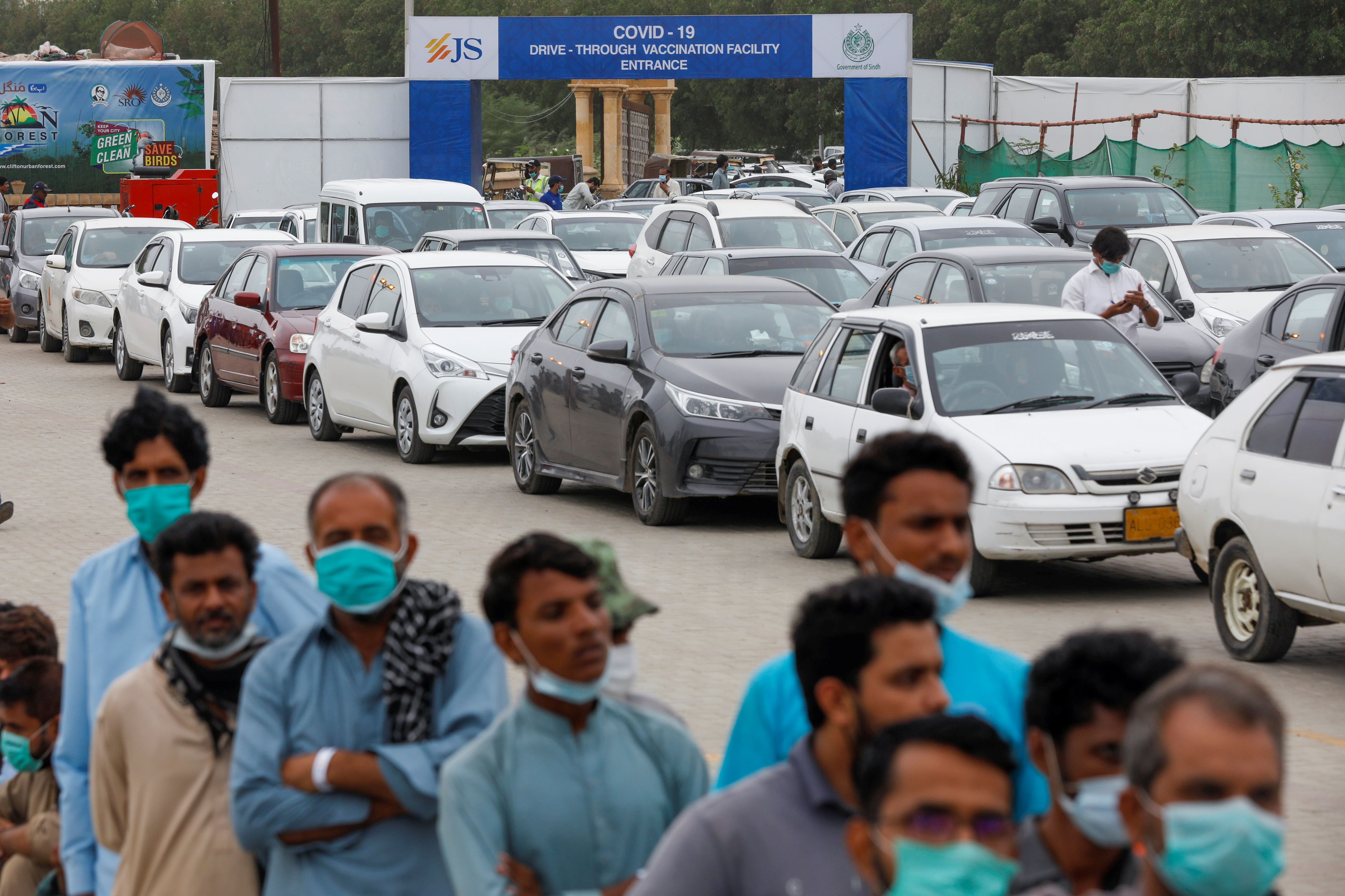Residents line up to receive  a vaccine against coronavirus disease (COVID-19) at a drive-through vaccination facility in Karachi, Pakistan July 29, 2021. REUTERS/Akhtar Soomro