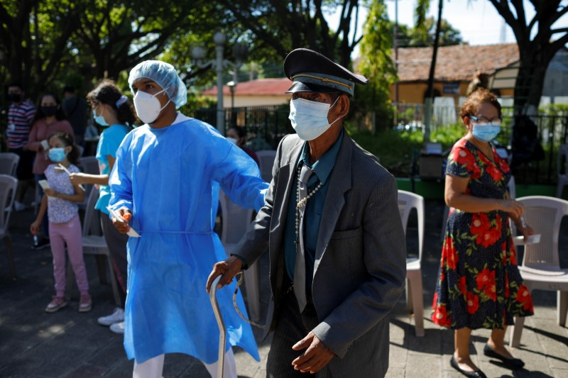 A medical worker helps a man to get tested for the coronavirus disease (COVID-19), after the government set up testing booths in Tecoluca, El Salvador August 1, 2021. REUTERS/Jose Cabezas