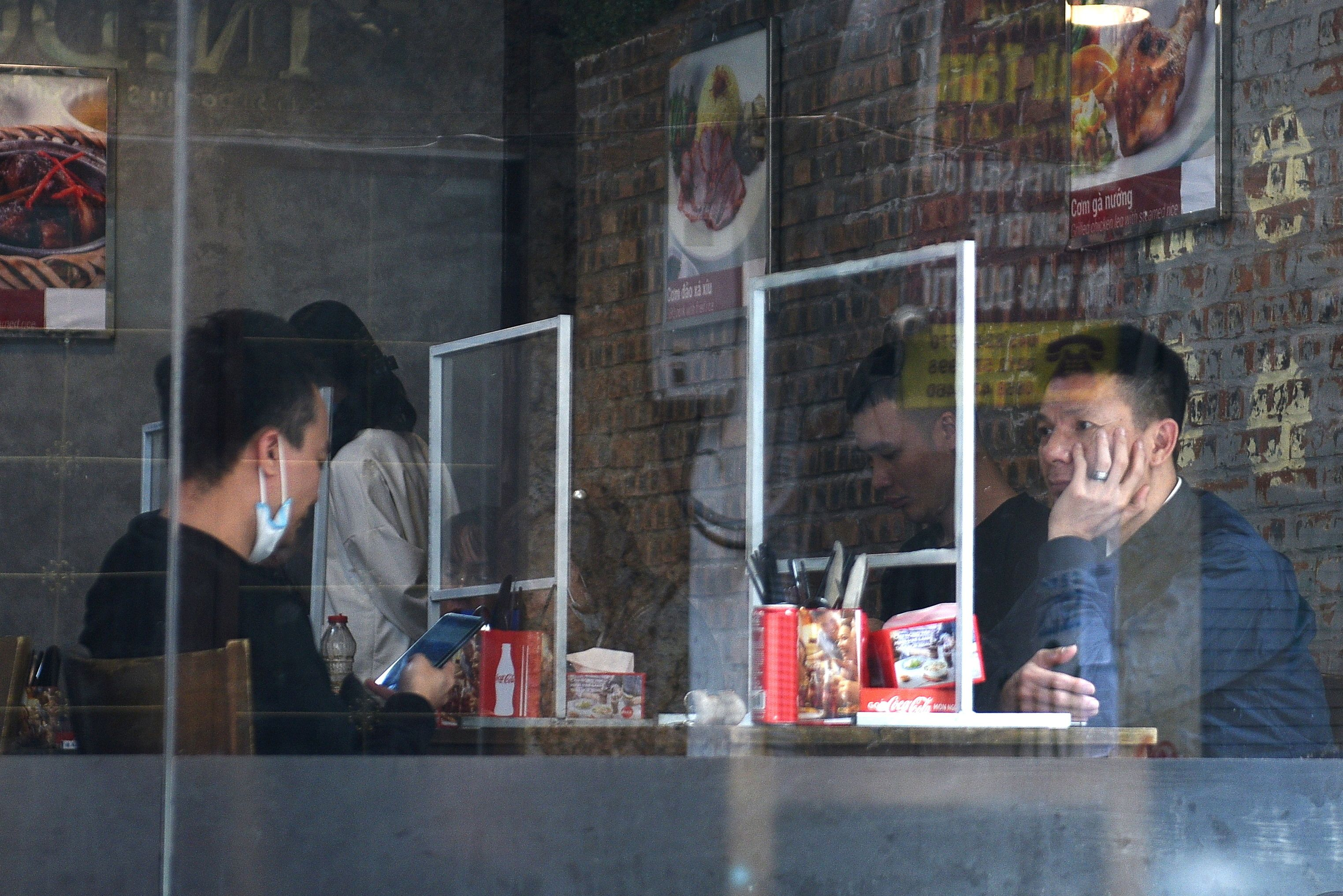 People sit in a restaurant behind plastic dividers as a measure against the sread of the coronavirus disease (COVID-19) in Hanoi, Vietnam, February 18, 2021. REUTERS/Thanh Hue/File Photo