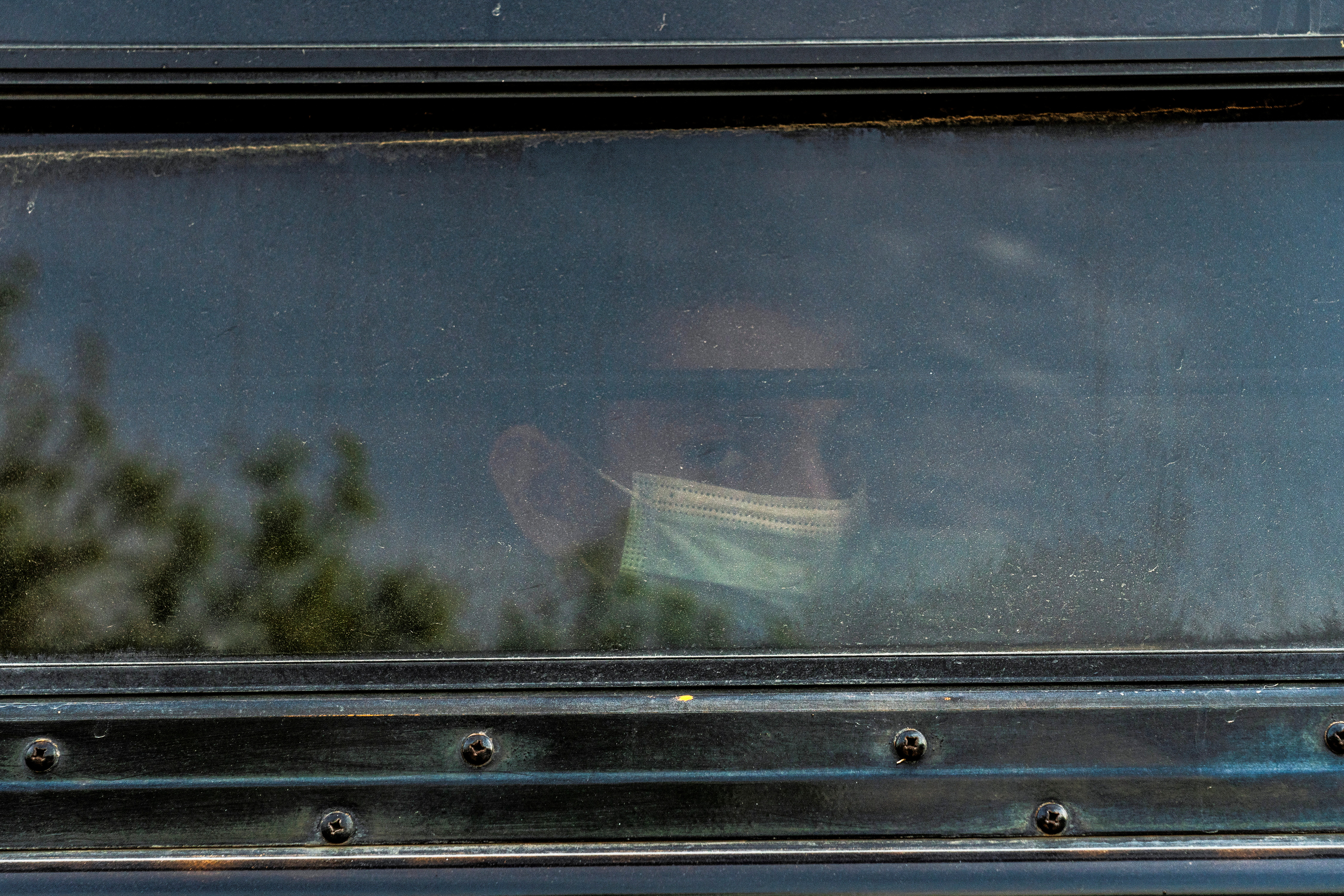 A young asylum-seeking migrant looks out from the window on a bus while waiting to be transported by the U.S. Border Patrols after crossing the Rio Grande river into the United States from Mexico in La Joya, Texas, U.S., March 26, 2021.  REUTERS/Go Nakamura