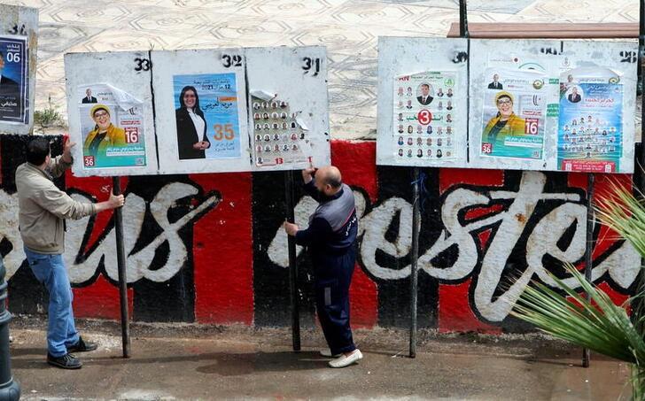People fix electoral panels ahead of the legislative elections, in Algiers, Algeria June 5, 2021. REUTERS/Ramzi Boudina
