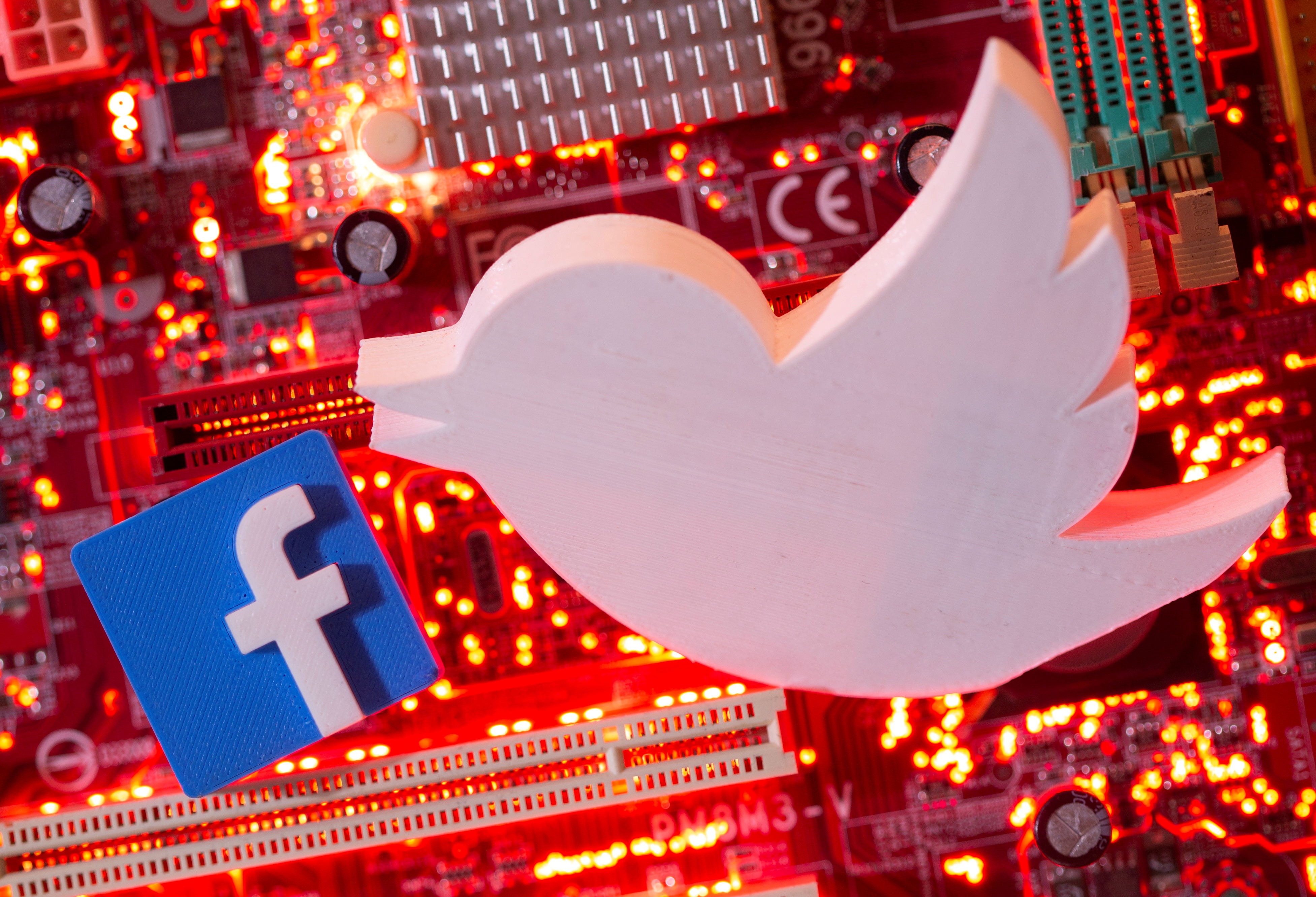 3D printed Facebook and Twitter logos are placed on a computer motherboard in this illustration taken January 21, 2021. REUTERS/Dado Ruvic/Illustration