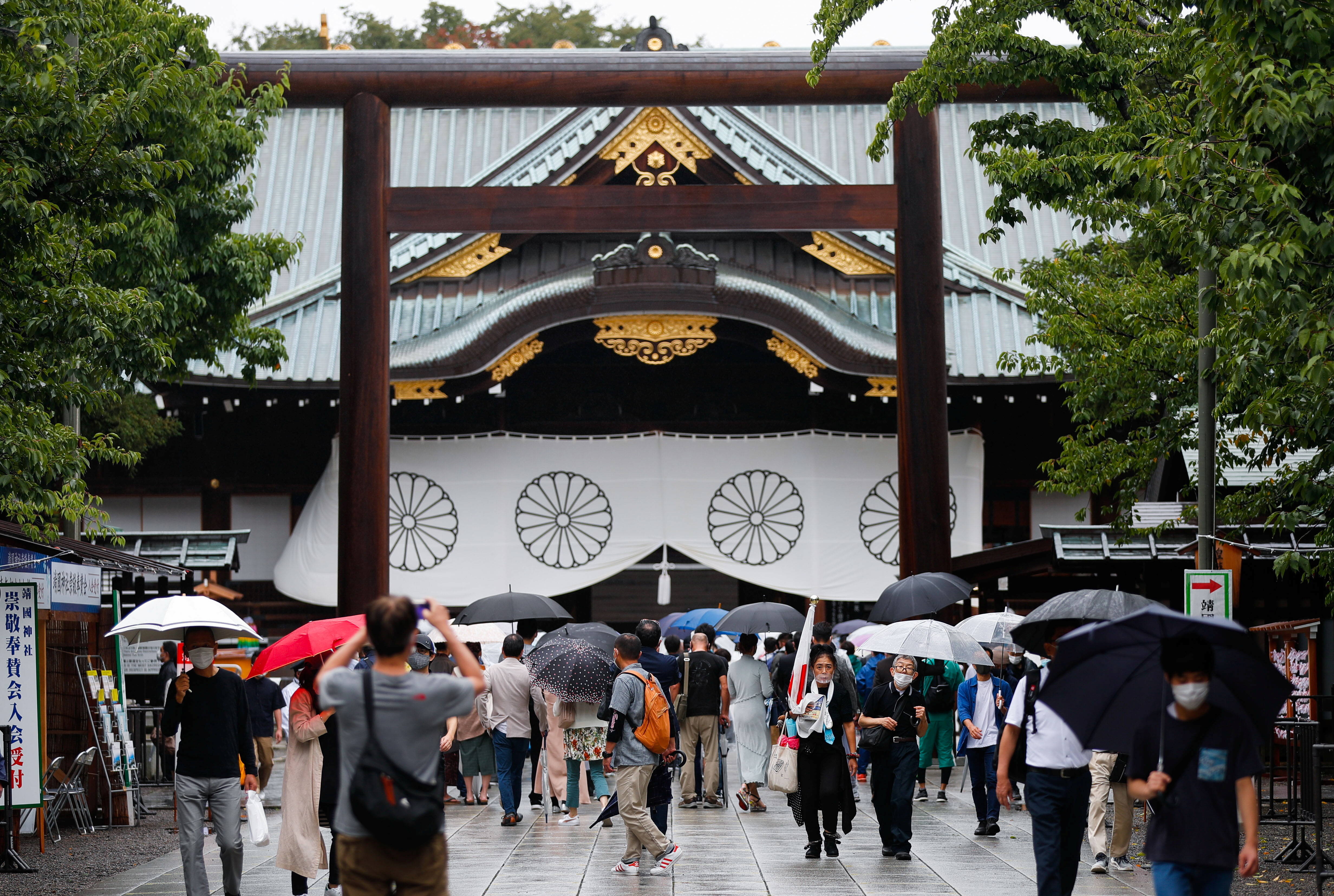 People carry umbrellas as they visit Yasukuni Shrine in Tokyo, Japan August 15, 2021. REUTERS/Issei Kato