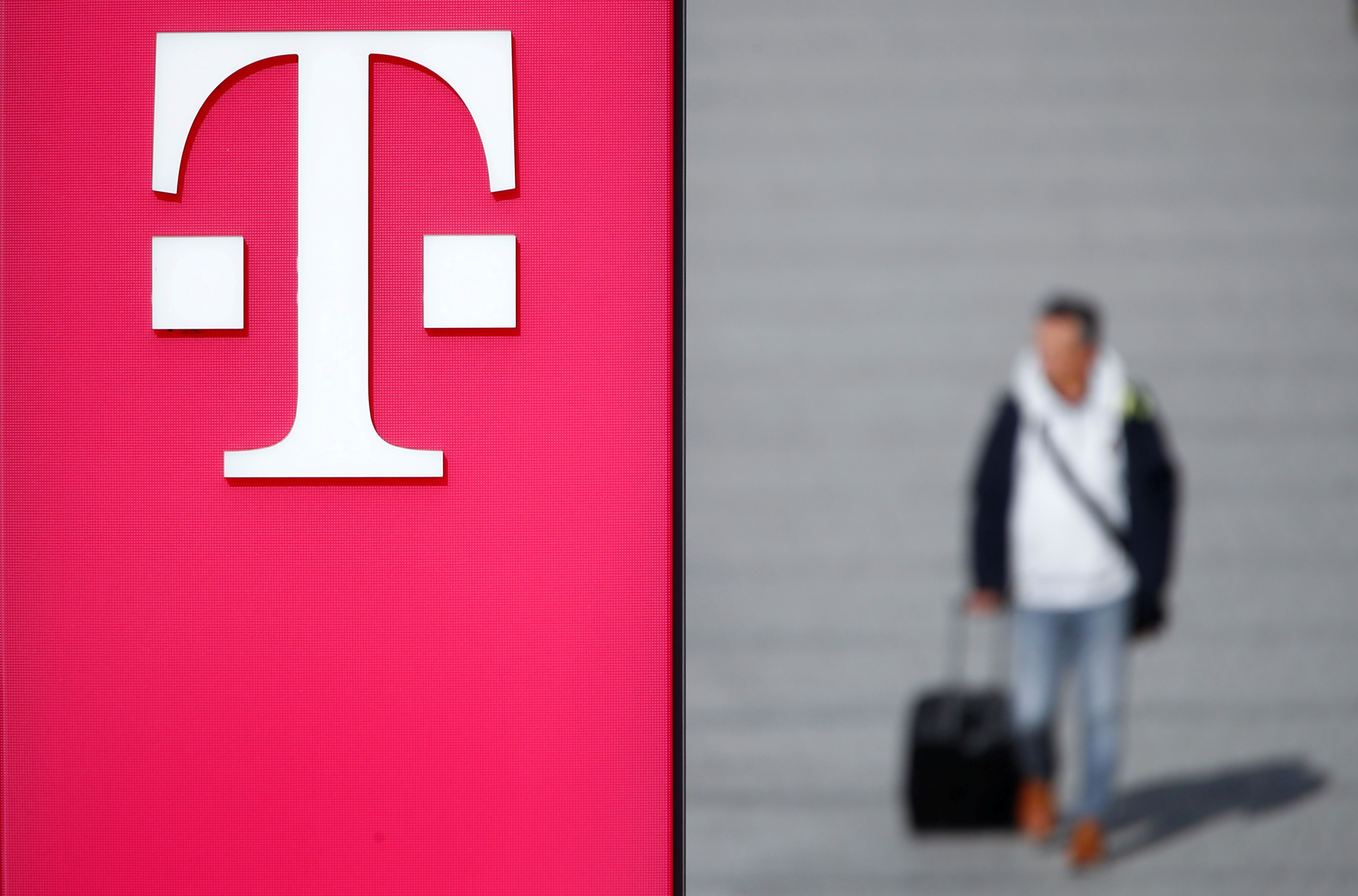 A man walks past the logo of Deutsche Telekom AG at the headquarters of German telecommunications giant in Bonn, Germany, February 19, 2019. REUTERS/Wolfgang Rattay/File Photo