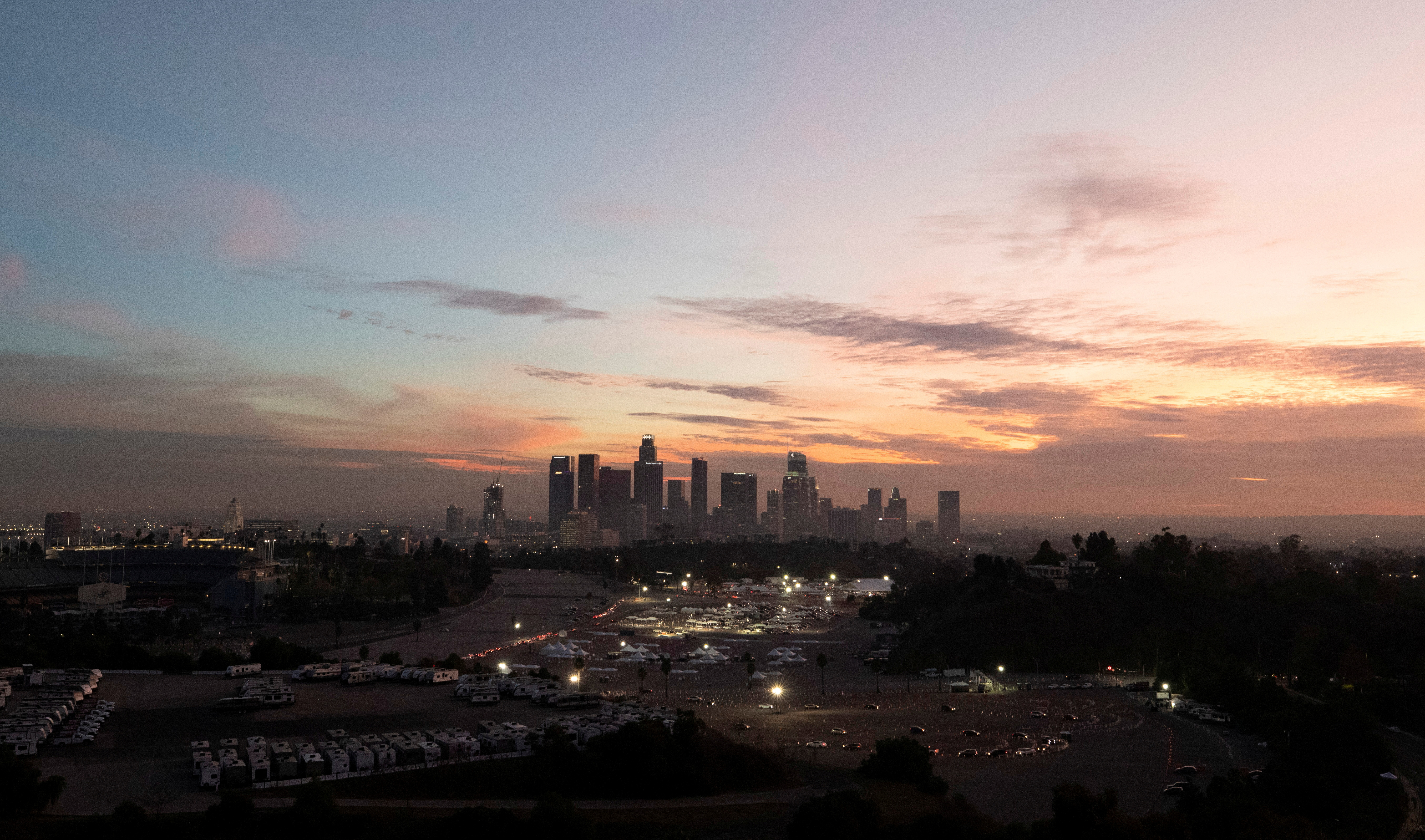 Vehicles line up at at Dodger Stadium COVID-19 vaccination site at sunset during the outbreak of the coronavirus disease (COVID-19), in Los Angeles, California, U.S., February 1, 2021. REUTERS/Mario Anzuoni/File Photo