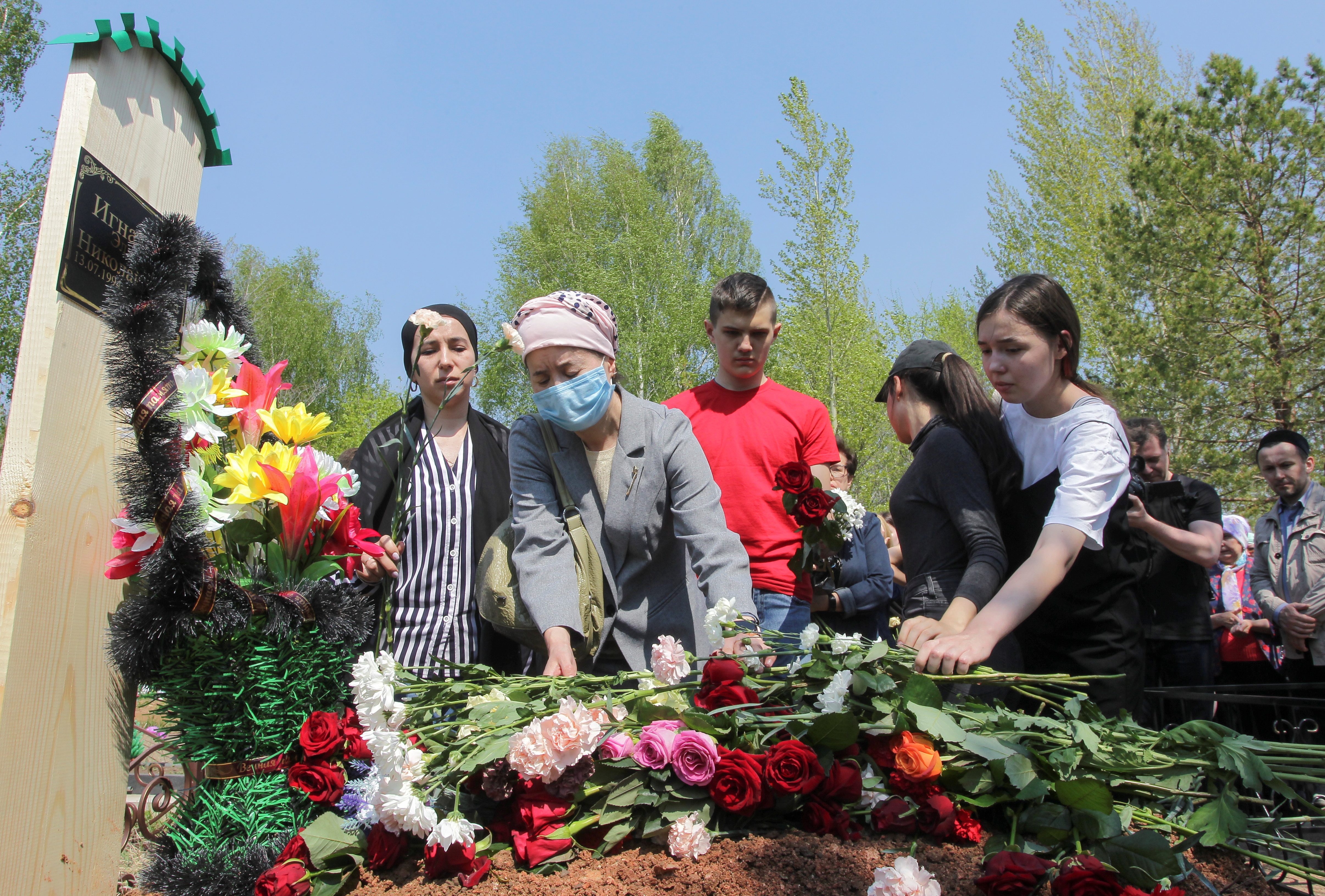 People mourn at the grave of Elvira Ignatieva, an English language teacher killed in the massacre at School Number 175, during a funeral at a cemetery in Kazan, Russia May 12, 2021. REUTERS/Alexey Nasyrov