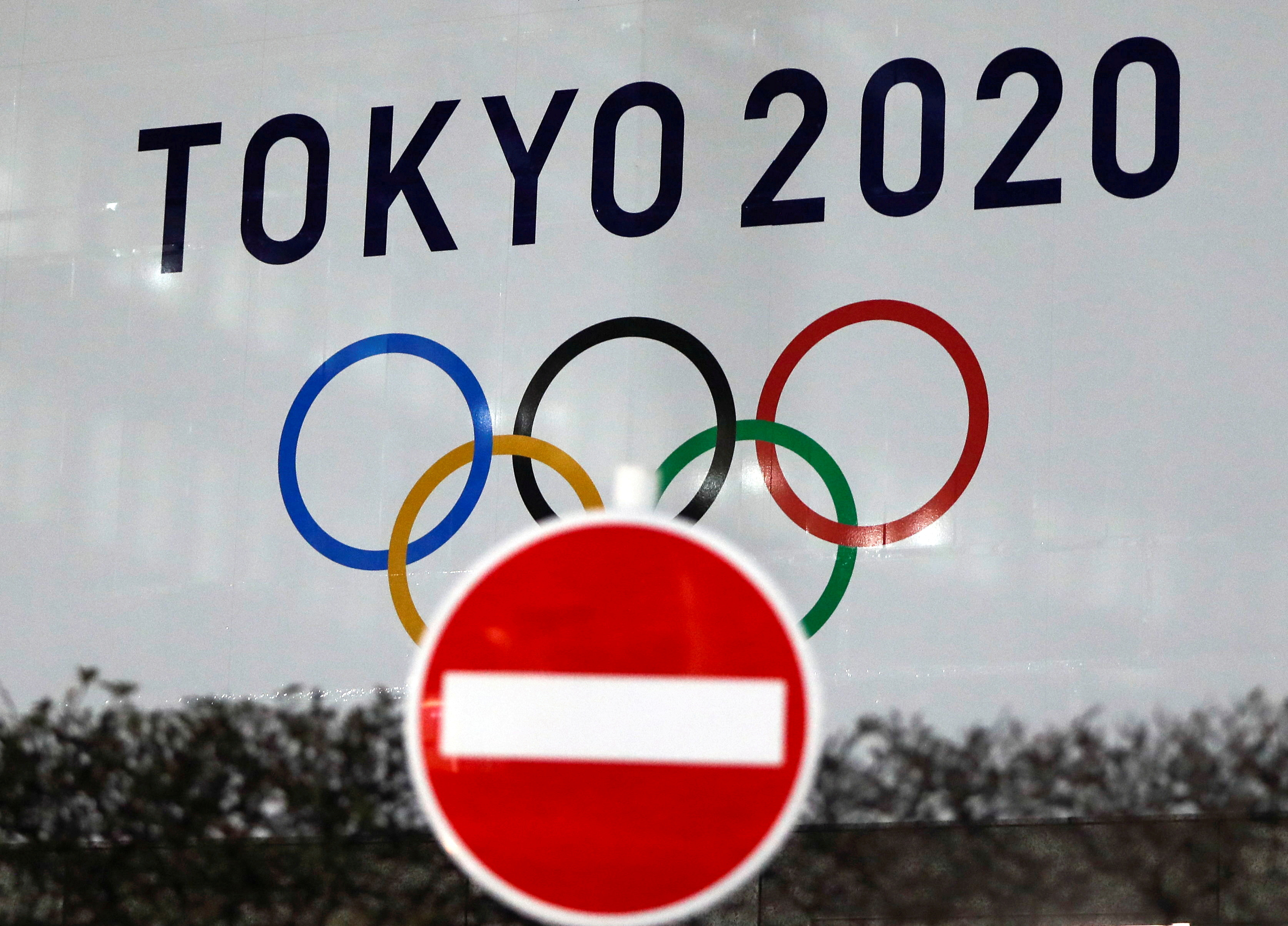 The logo of Tokyo 2020 Olympic Games that have been postponed to 2021 due to the coronavirus disease (COVID-19) outbreak, is seen through a traffic sign at Tokyo Metropolitan Government Office building in Tokyo, Japan January 22, 2021. REUTERS/Issei Kato/File Photo/File Photo