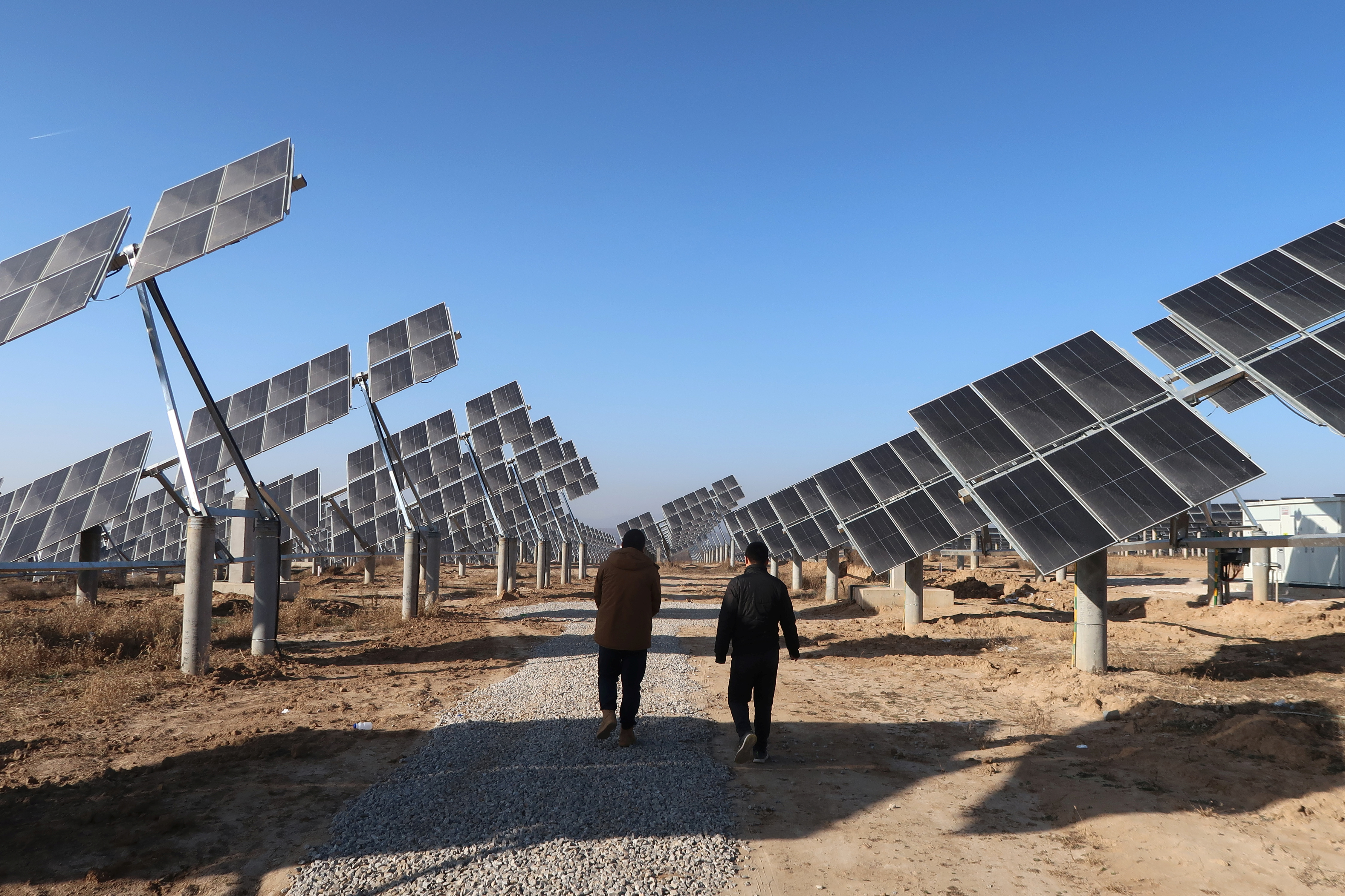 Workers walk at a solar power station in Tongchuan, Shaanxi province, China December 11, 2019. Picture taken December 11, 2019. REUTERS/Muyu Xu