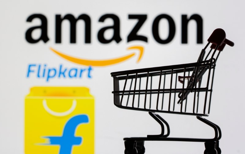 Small toy shopping cart is seen in front of displayed Amazon and Flipkart logos in this picture illustration taken, July 30, 2021. REUTERS/Dado Ruvic/Illustration/File photo